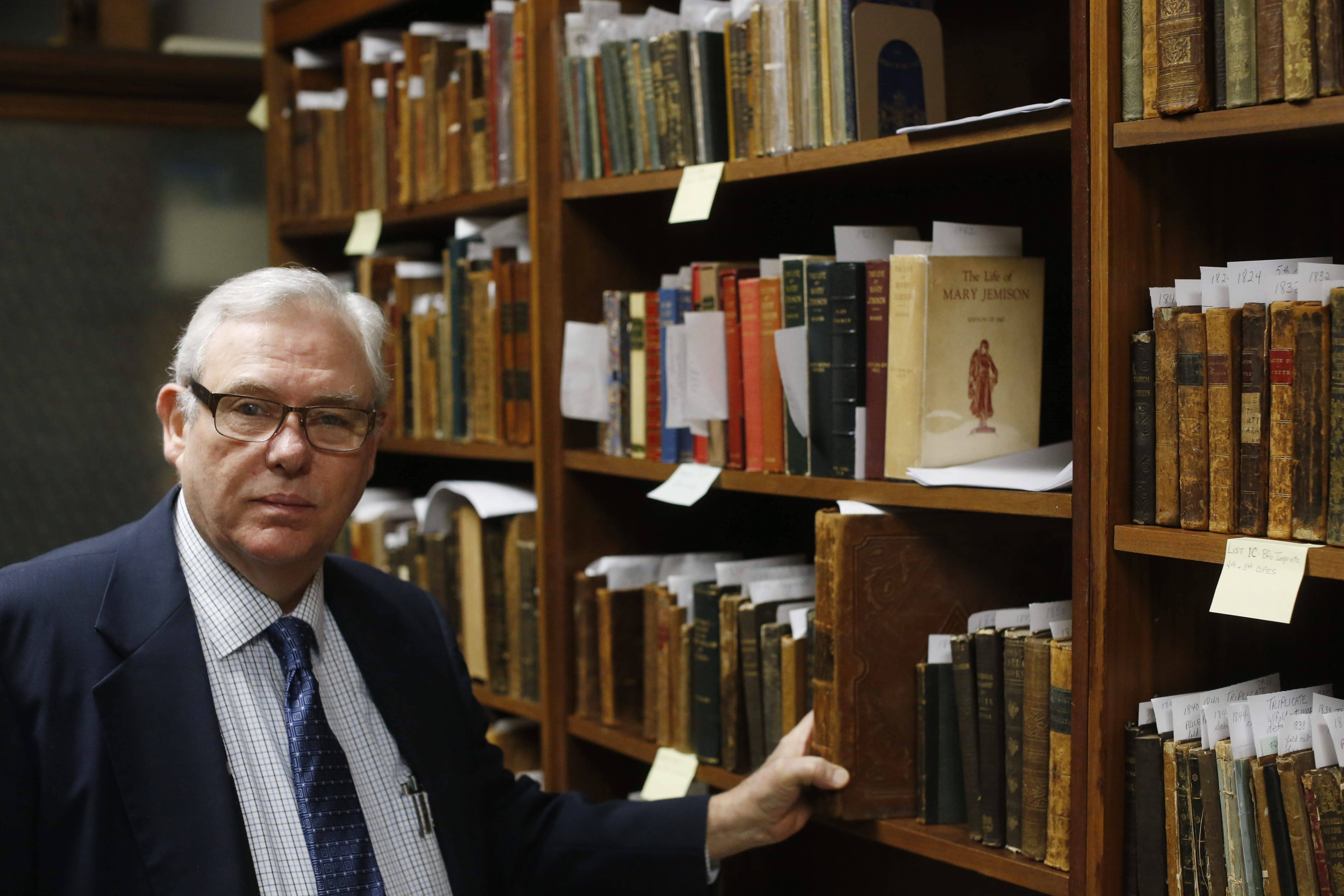 Ronald Cozzi, president of Old Editions Book Shop, looks through some of the 600 books in the collection of the late Eugene Musial, who amassed the largest collection of rare books printed in Buffalo in the 1800s. The collection is now for sale.