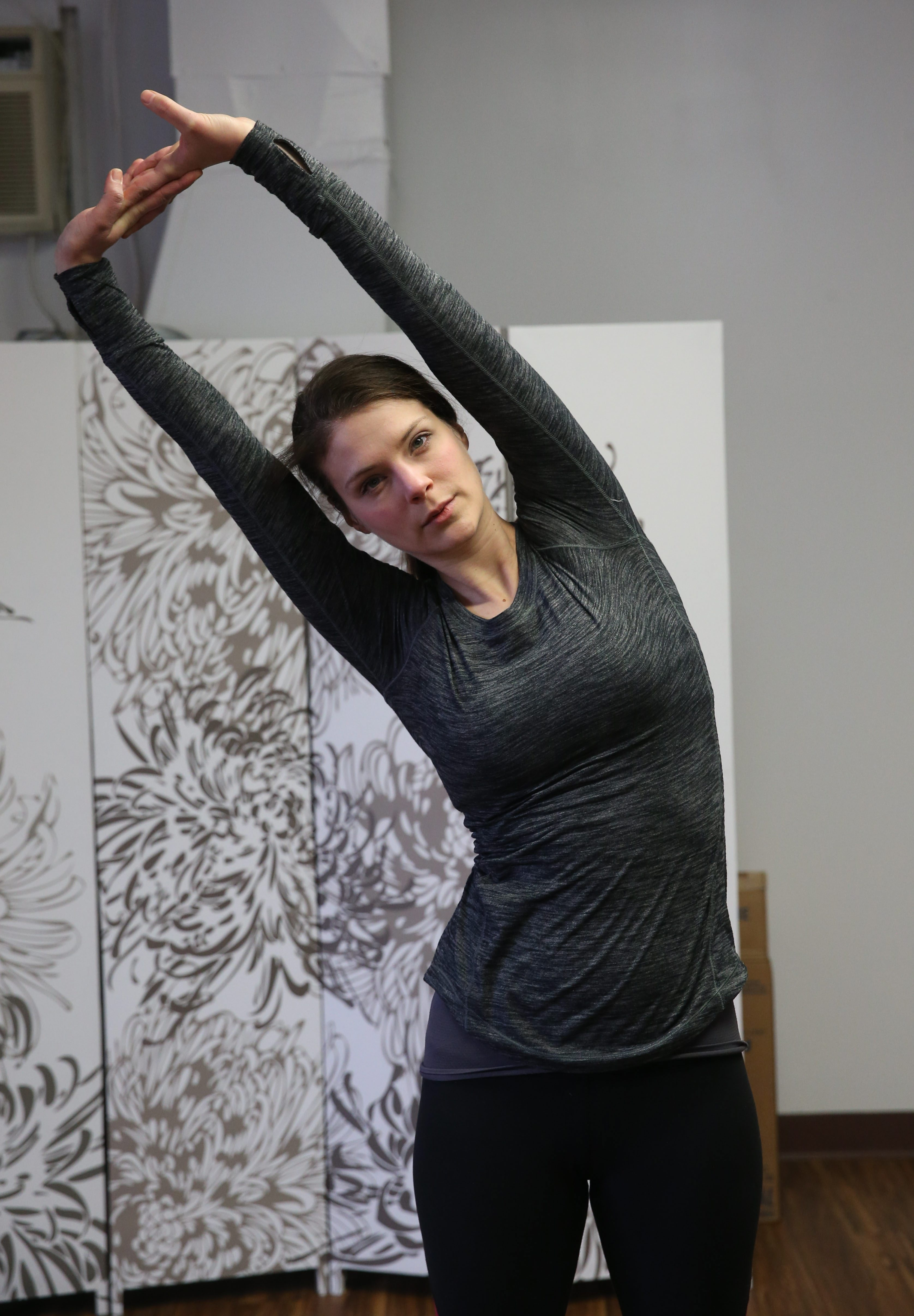 Hayley Sunshine, owner of Long + Lean Pilates at 515 Elmwood Ave. in Buffalo demonstrates some stretches that will help runners get ready for their season, Monday, Feb. 22, 2016.  This is the Overhead Side-Bend. (Sharon Cantillon/Buffalo News)