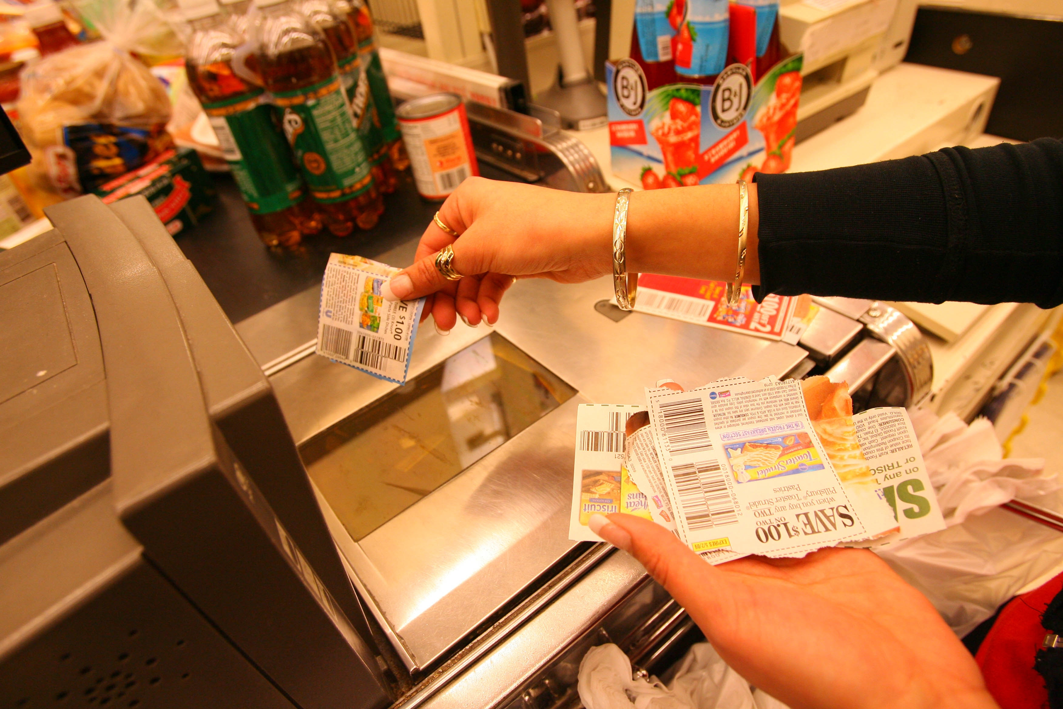 A Tops cashier scans customer coupons during one of the many and varied transactions that take place in its supermarkets daily. With a move to data analytics, the company has found opportunities to better allocate its personnel and cut down on wait times.