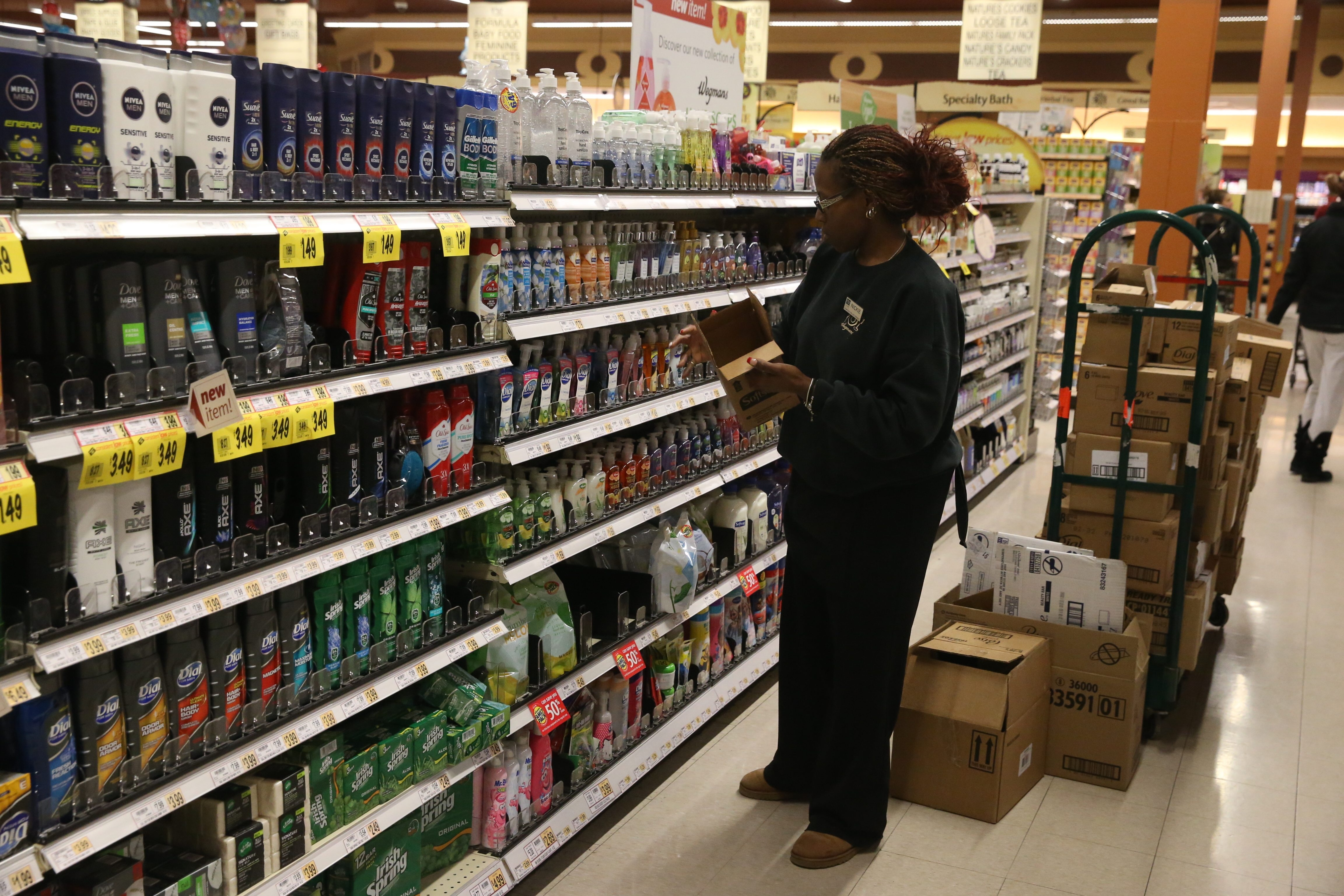 Nickie Crockett stocks shelves at Wegmans on Amherst Street. The grocery chain raised its score in customer satisfaction.