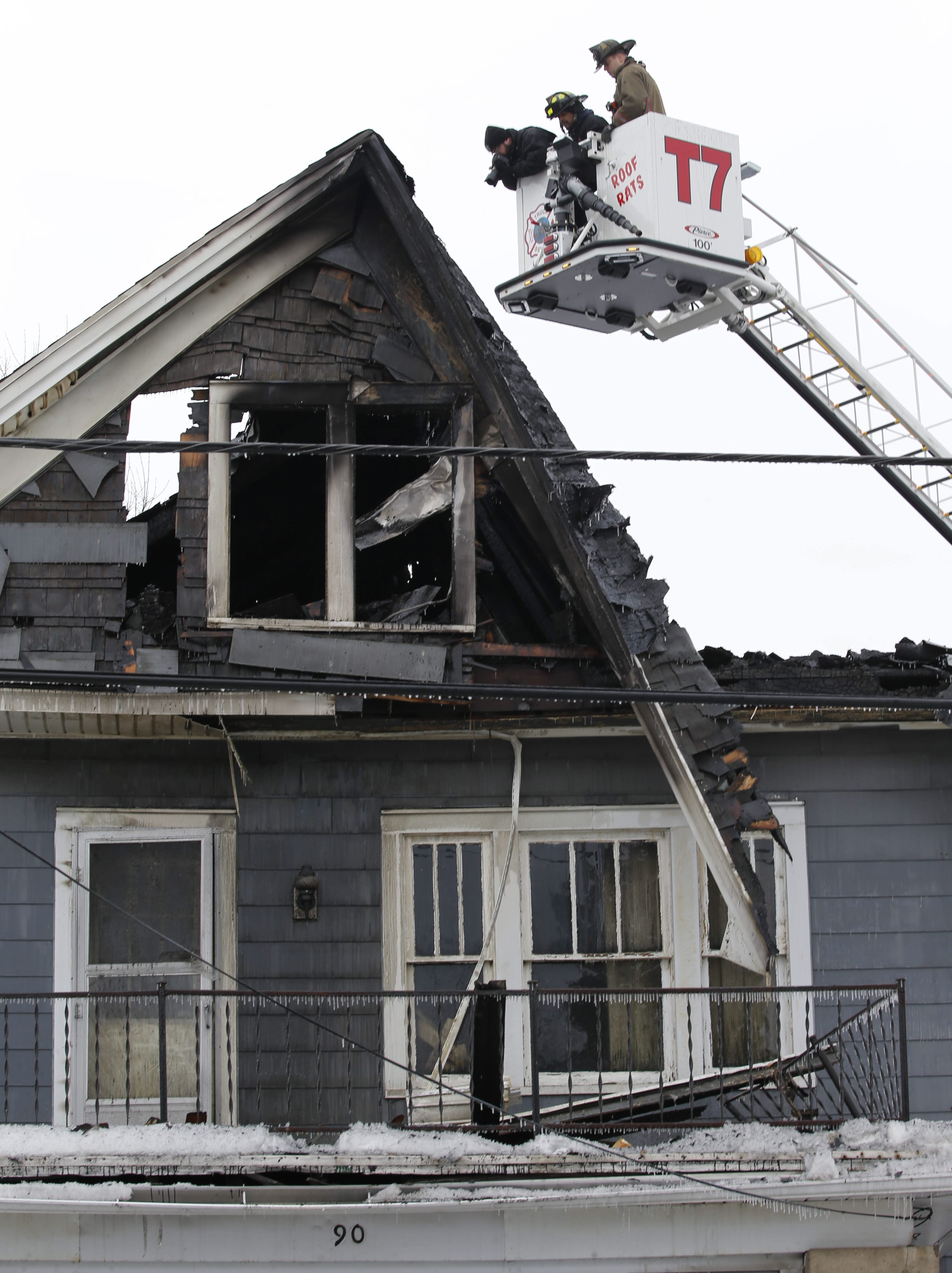 Police and fire investigators use a ladder truck to collect photographic evidence of Friday's fire.