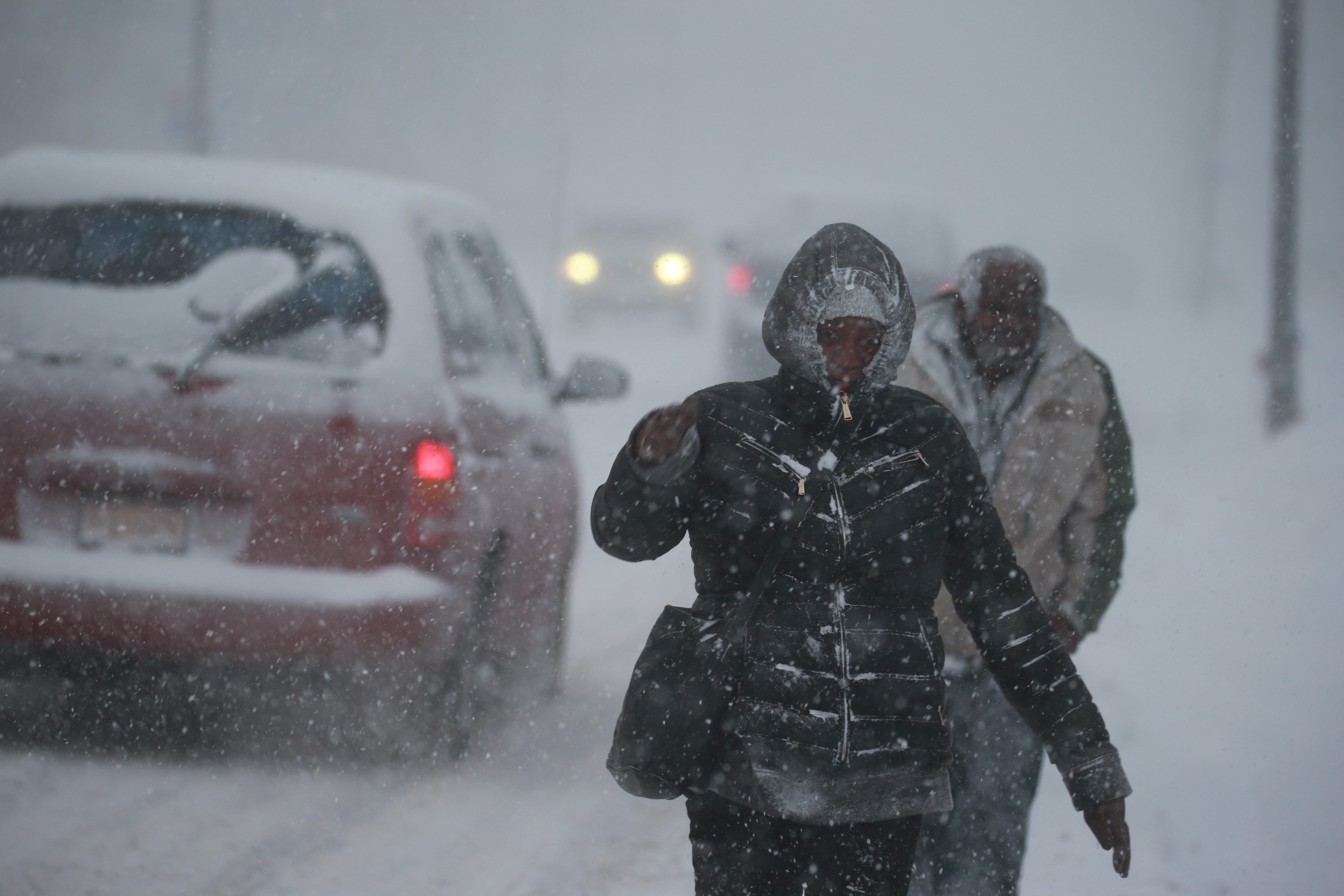 Tiffany Huff and Alvin Brown walk down Walden Avenue in Buffalo on Feb. 12, as TV news stations went into overdrive on storm coverage.