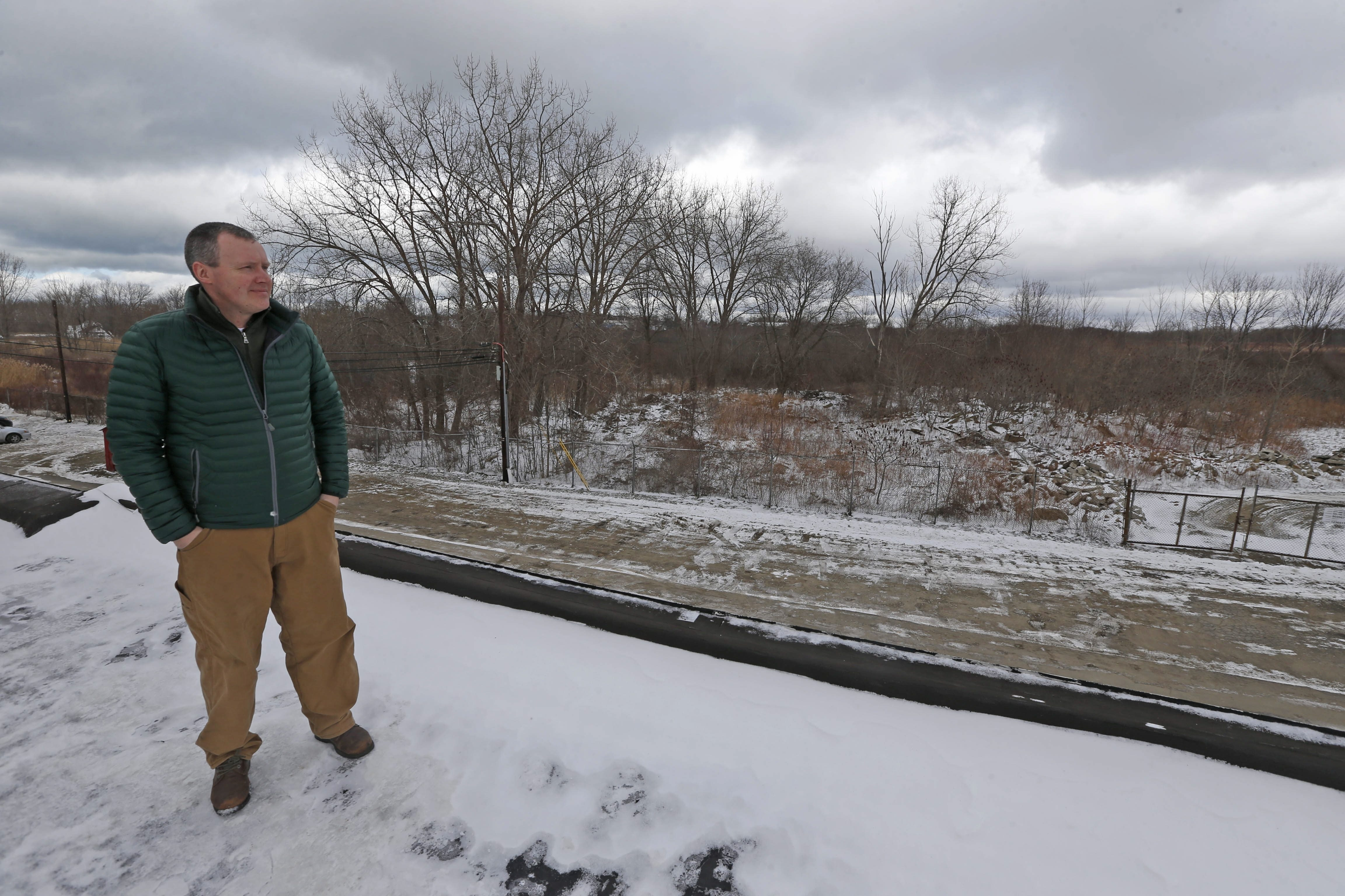 Patrick Stokes, a manager with Muldowney Development, looks out over the 12 acres, a portion of the total 32 acres obtained,  that executives with his company sold for the footprint of the new Athenex project location near 3817 Lake Shore Drive in the Town of Dunkirk. (Robert Kirkham/Buffalo News)