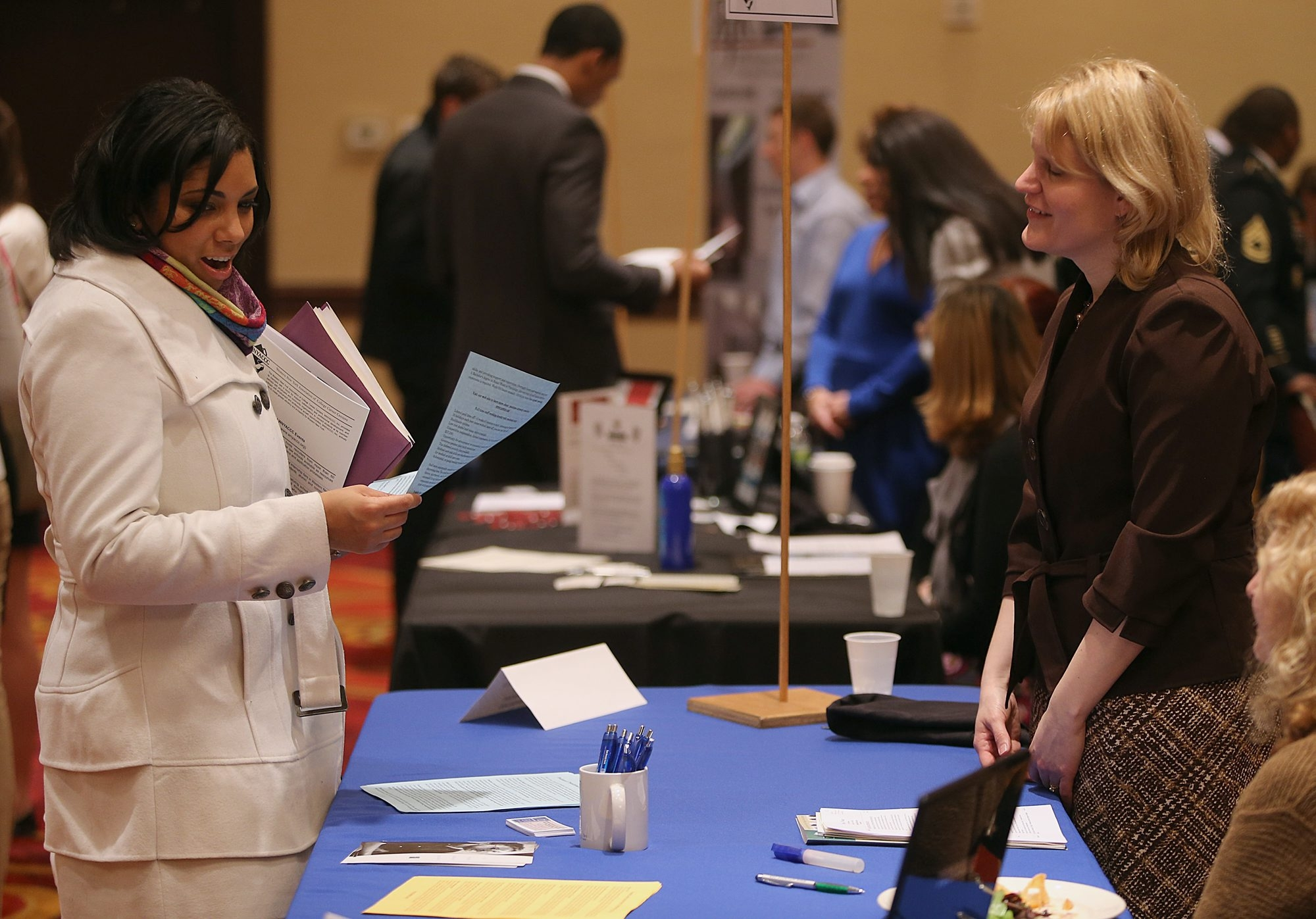 A job seeker looks over materials she received from a human resources manager at an Amherst jobs fair. Finding work still isn't easy, as employers are cautious about hiring in an economy that's growing, but slowly.
