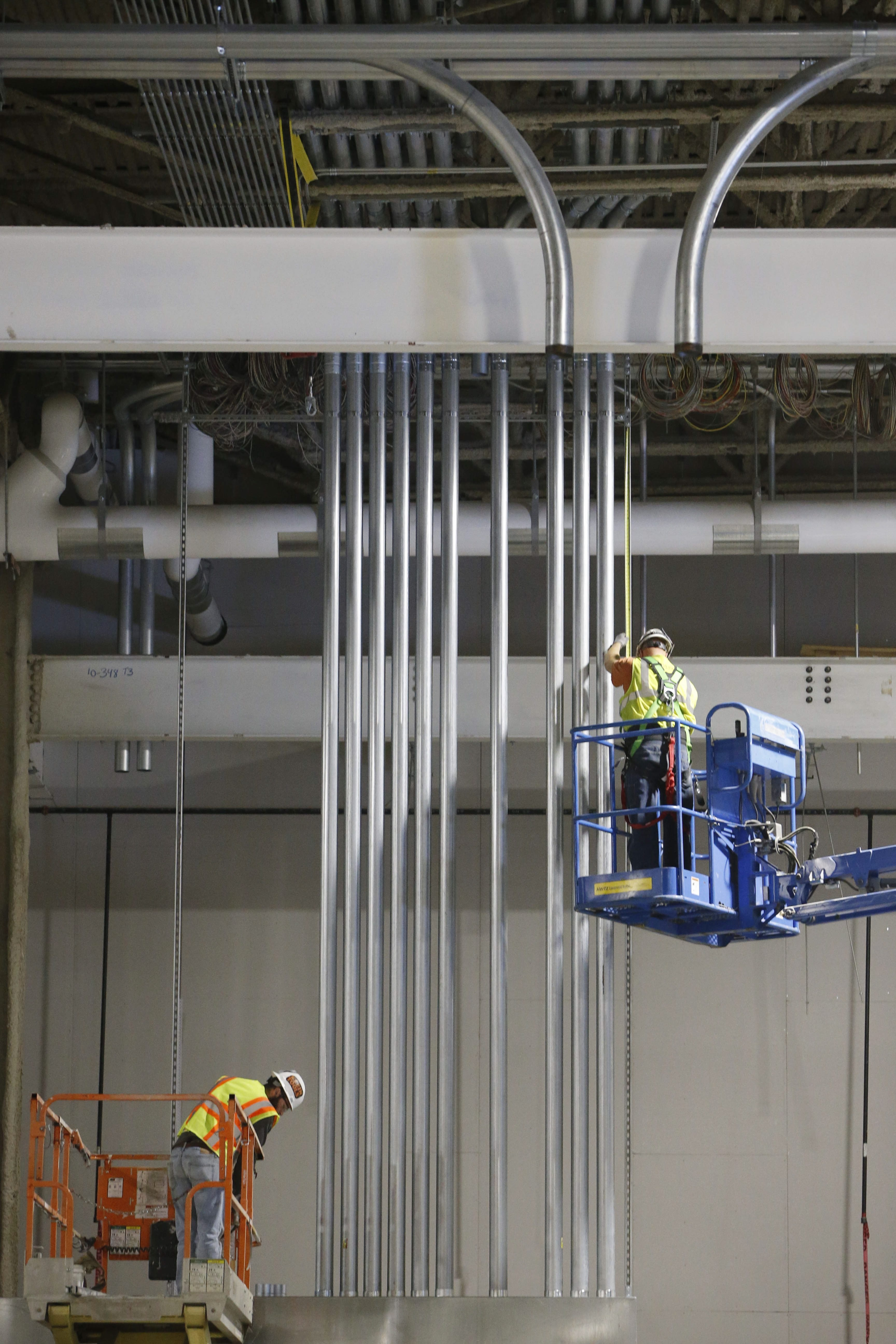 Workers, top photo, install an elaborate system of conduits to regulate the purity of water and air used in the manufacture of solar panels. Below, workers install tanks for the water purification system as construction of the enormous SolarCity factory continues at RiverBend early in January. The construction crew is expected to peak at up to 1,100 workers.