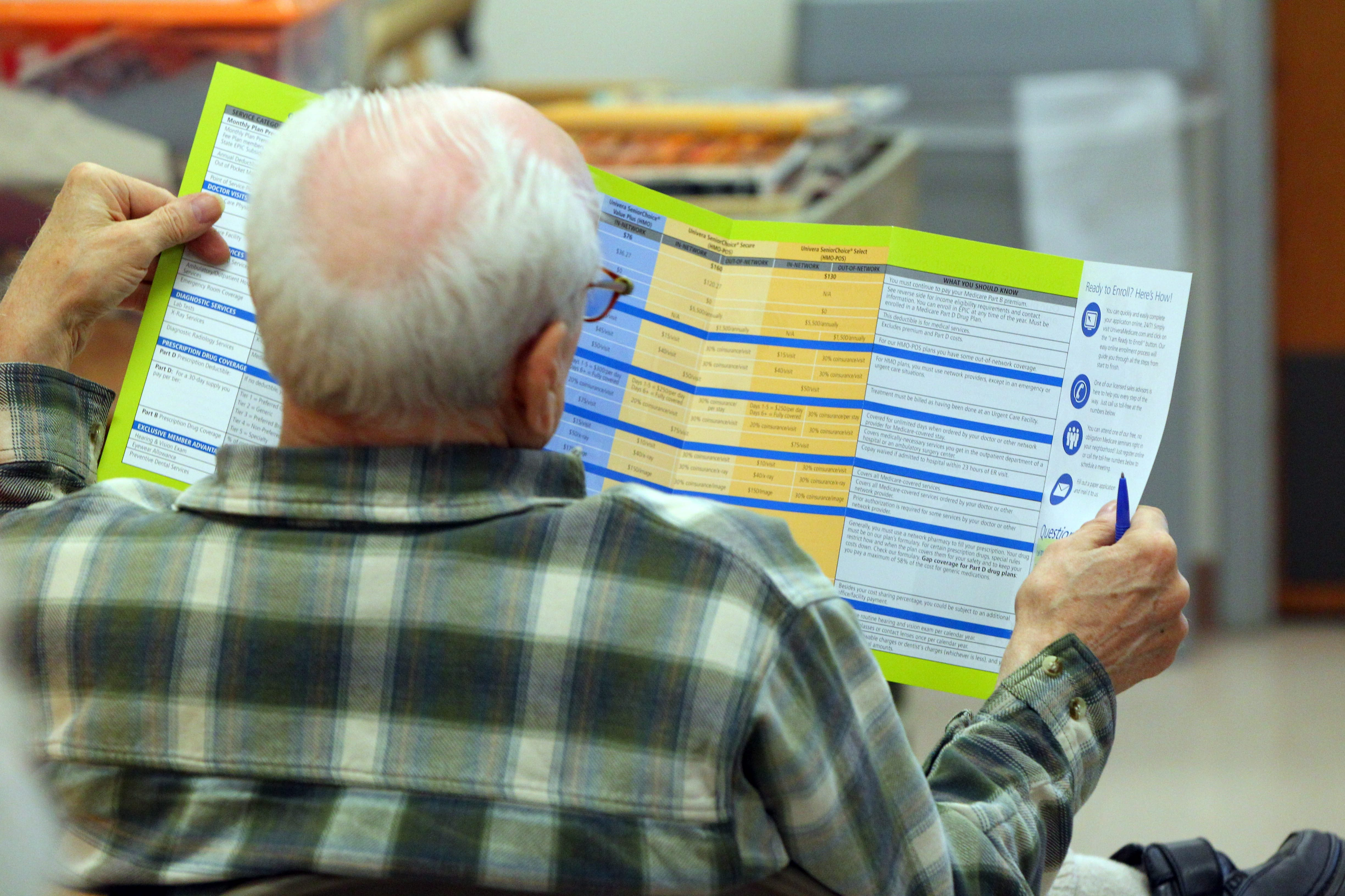 A senior citizen looks over Medicare options, an often frustrating and confusing exercise.