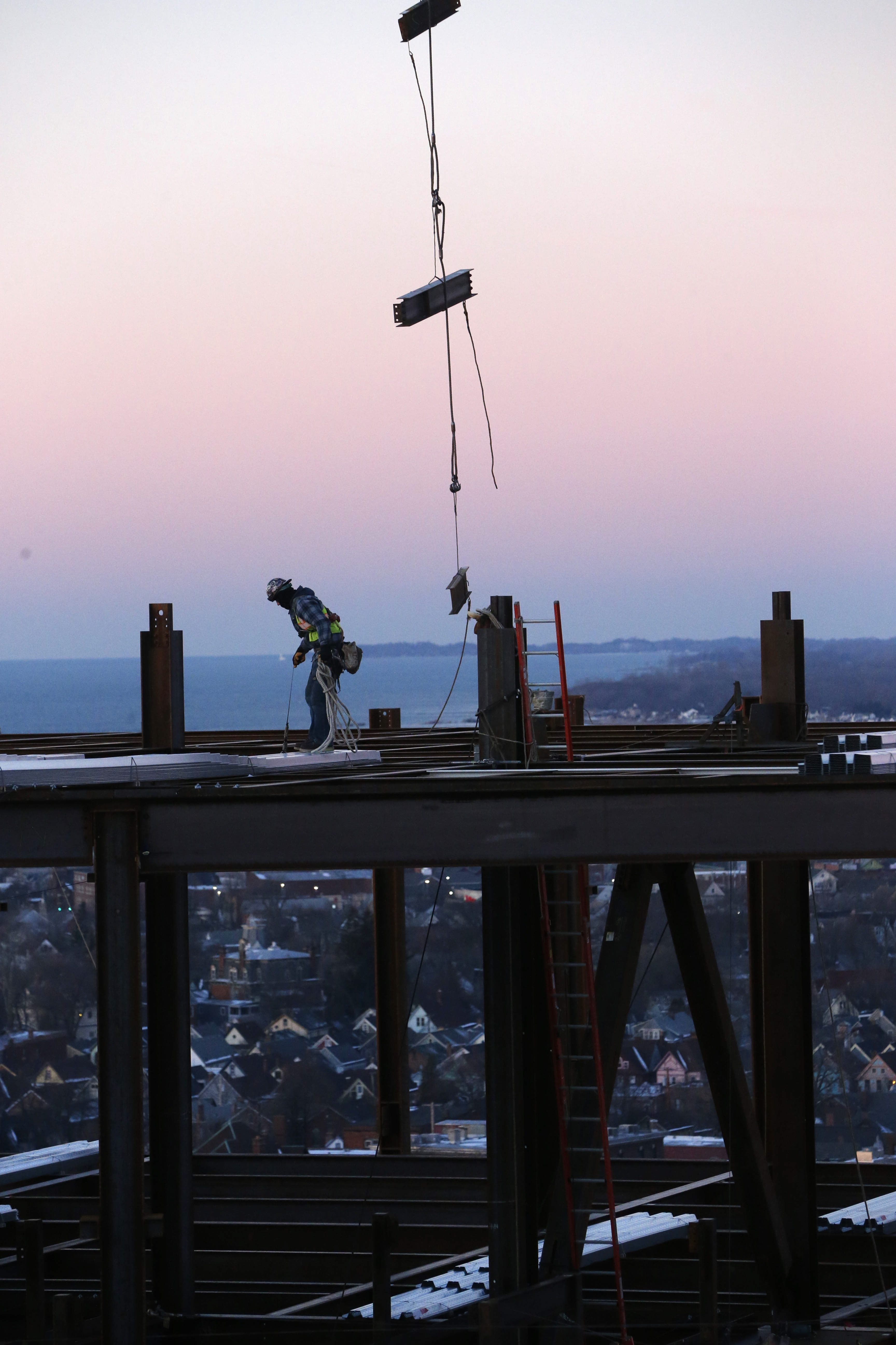 Iron workers position beams on the top of the steel frame of the new Children's Hospital on the Buffalo Niagara Medical Campus.