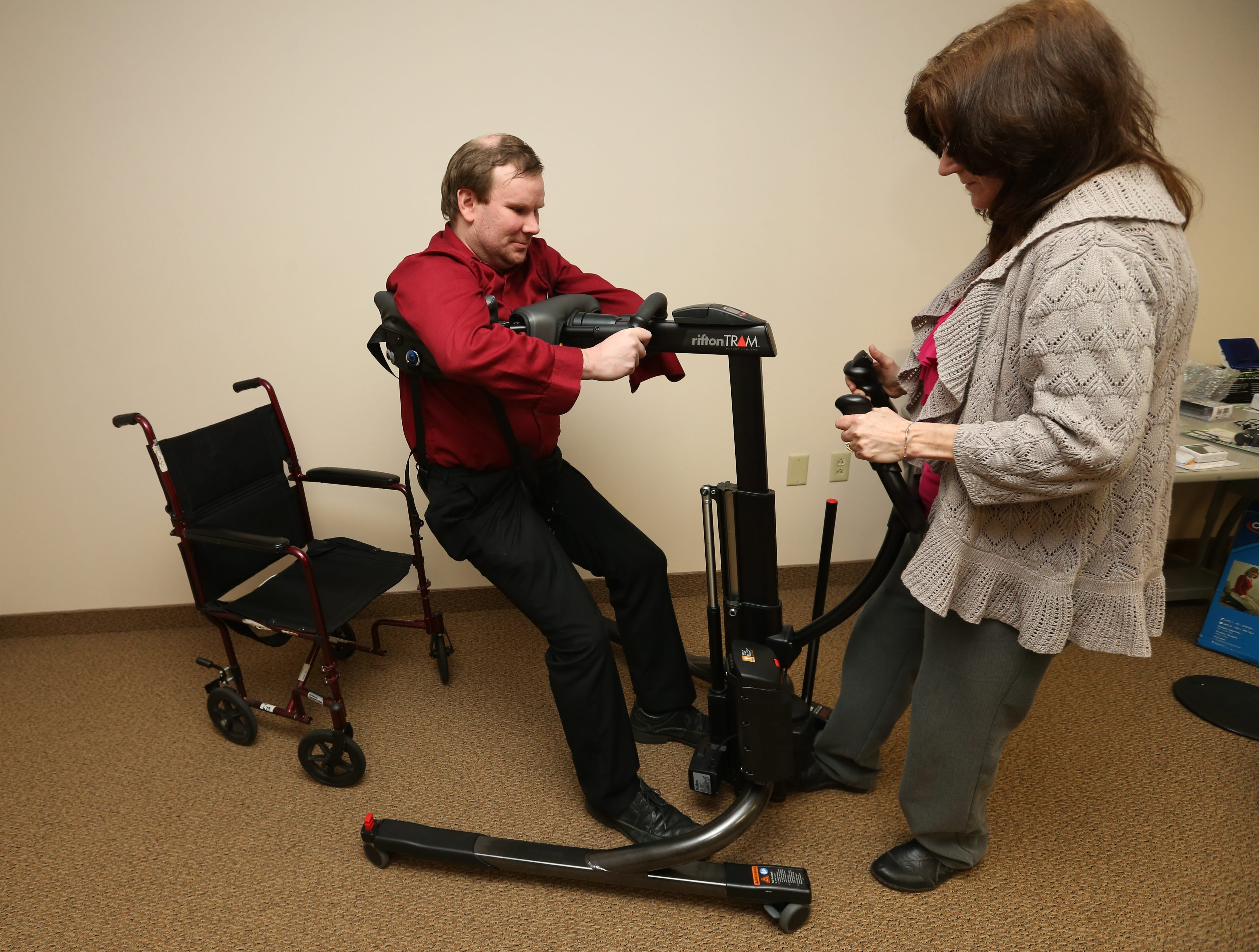 At top, Kim Naus, coordinator of client services at the University at Buffalo Center for Assistive Technology,  demonstrates the adaptive pillow switch, the standing lift and the stand and pivot board with occupational therapist Nathan Ramsey. Above, left, devices for the dining table include a plate with a suction bottom that keeps it from tipping over and the weighted utensils that help Parkinson's patients to keep steady while eating. At right is the Doormatic, a device that converts a standard door into an automatic door.
