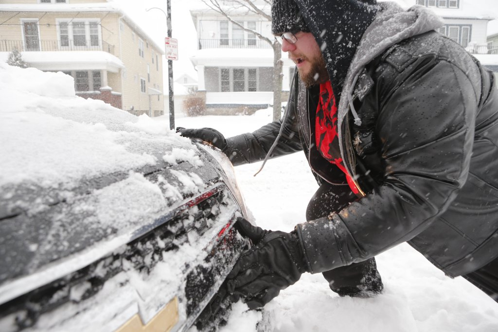 Michael Jakubczak pushes his mother's car out of the driveway on Norwalk Avenue in North Buffalo on Feb. 16. (Derek Gee/Buffalo News)