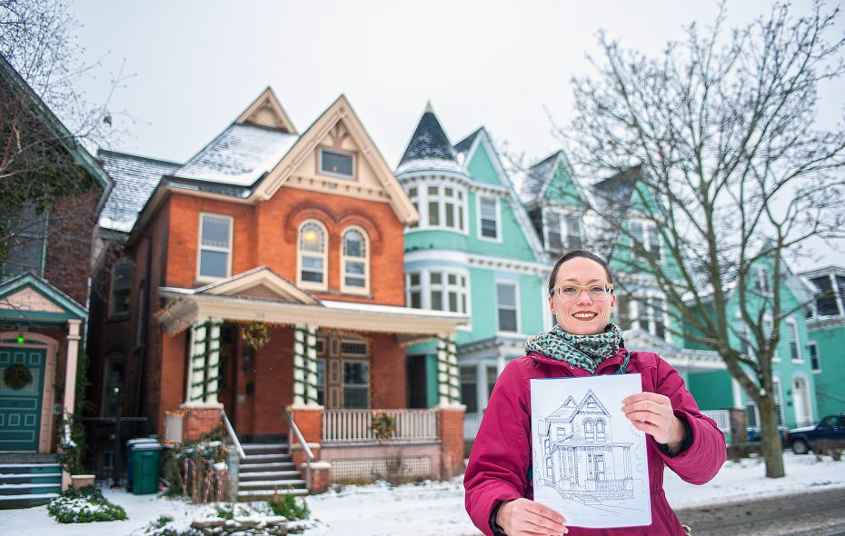 Dana Saylor shows a page from her Allentown Architecture coloring book in front of the historic home that inspired it. (Michael P. Majewski)