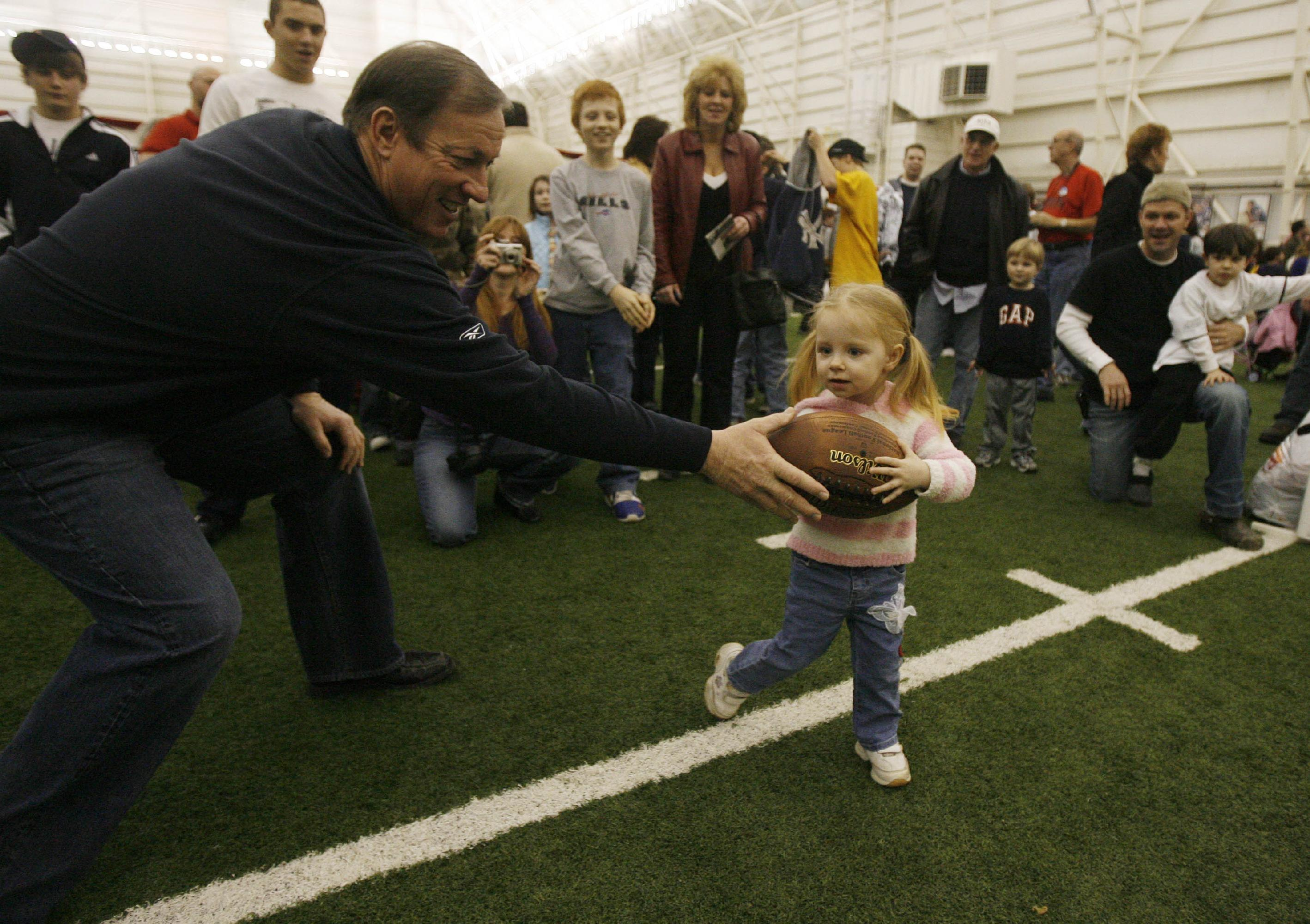 Buffalo Bills Hall of Fame Quarterback Jim Kelly hands off to Tiffany Nowak, 2, during Hunter's Day of Hope festivities  on Feb. 14, 2009. This year's event takes place Saturday at ADPRO Sports Training Facility  at Ralph Wilson Stadium in Orchard Park. (Mark Mulville/Buffalo News file photo)