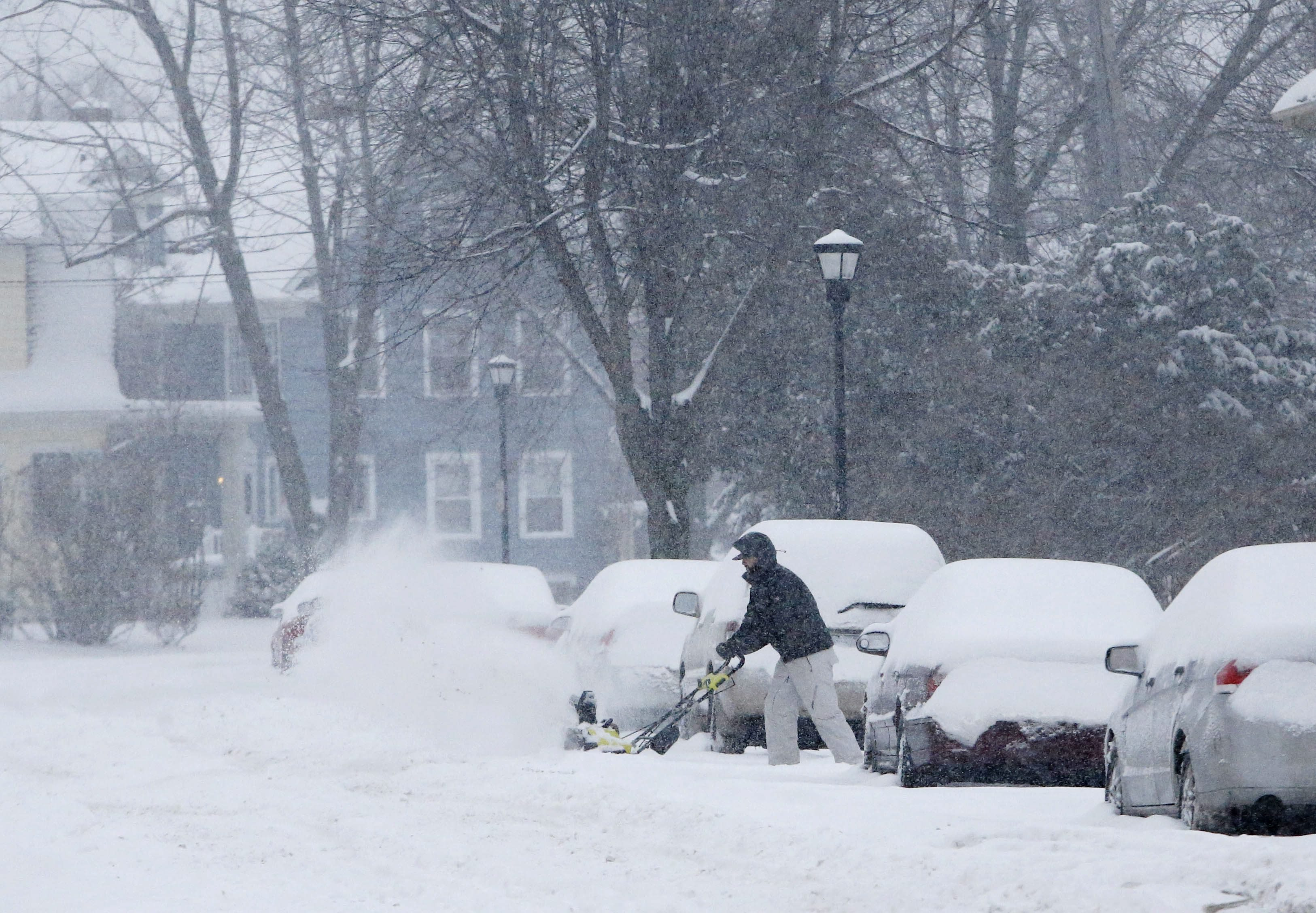 A man uses a snowblower to clear out a driveway on Saranac Avenue in North Buffalo on Feb. 16. (Derek Gee/Buffalo News)