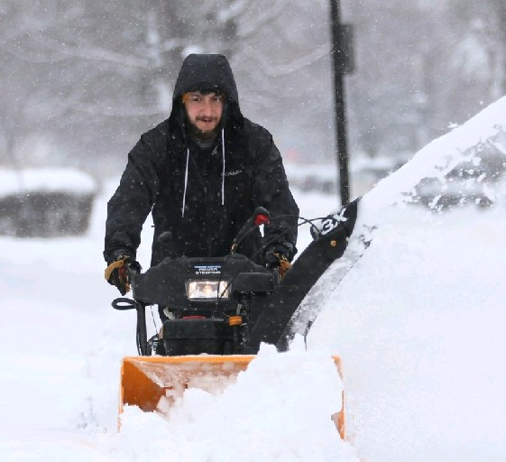 A local resident clears the snow from a mid-week storm that set a record on Tuesday for snowfall on Feb. 16. (Sharon Cantillon / Buffalo News)