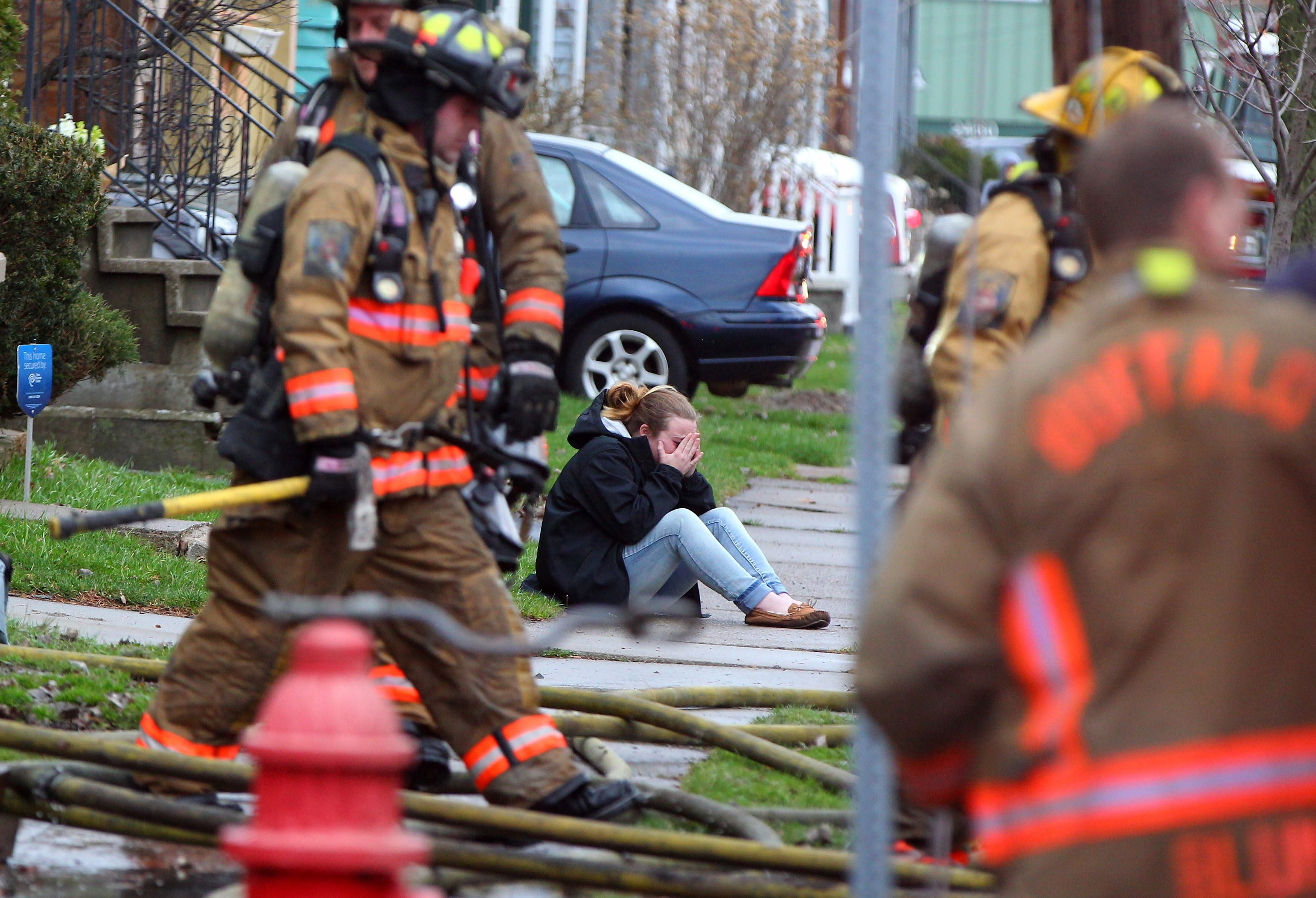 A person grieves as Buffalo firefighters work on a house fire on Wildwood Pl in Buffalo Thursday, March 31, 2016.   (Mark Mulville/Buffalo News)