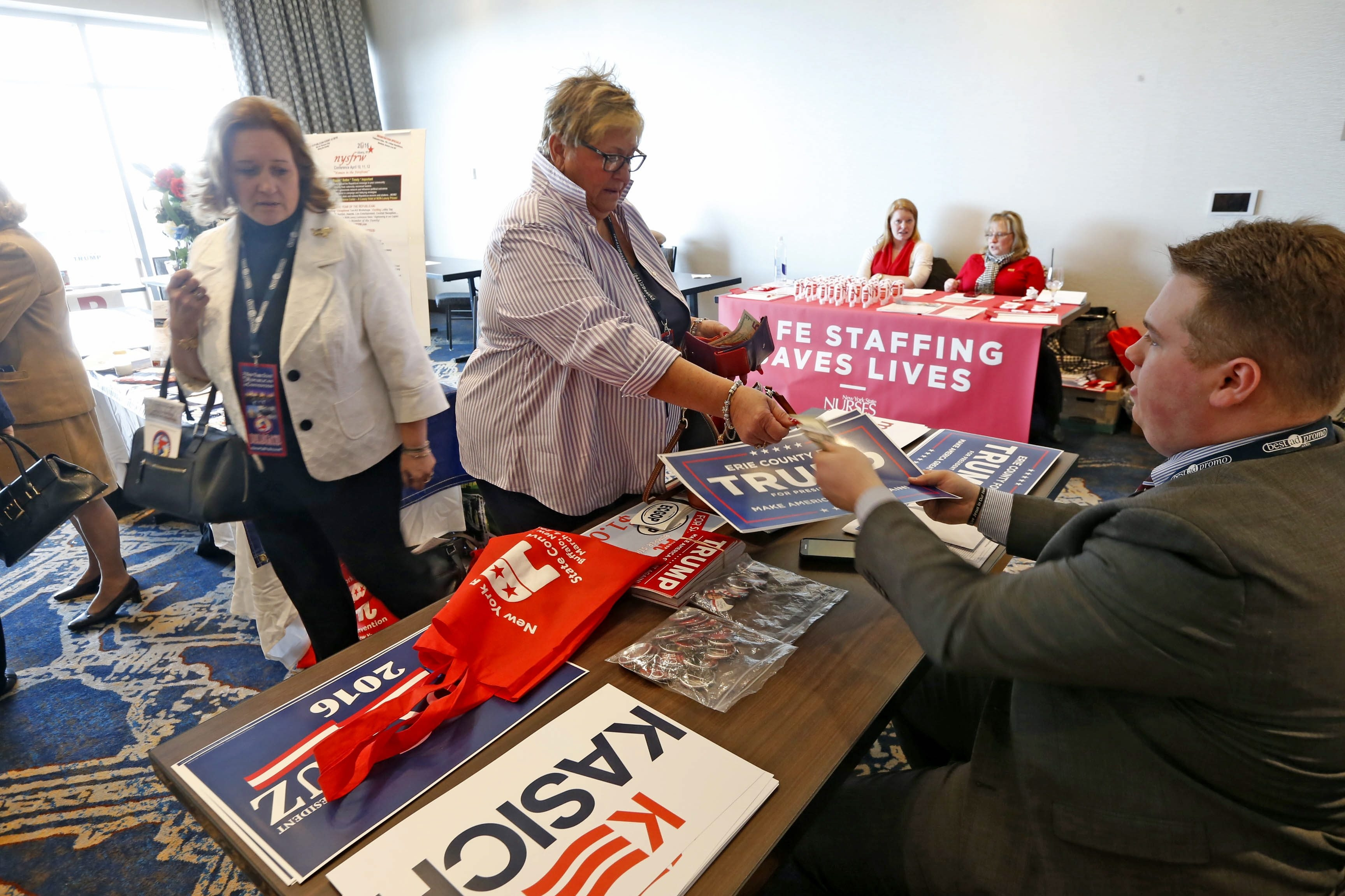 Matt Braun, right, hands a Trump placard to Christine Pilozzi of the City of Tonawanda on Friday as the New York State Republican Convention got underway at the Marriott HarborCenter.
