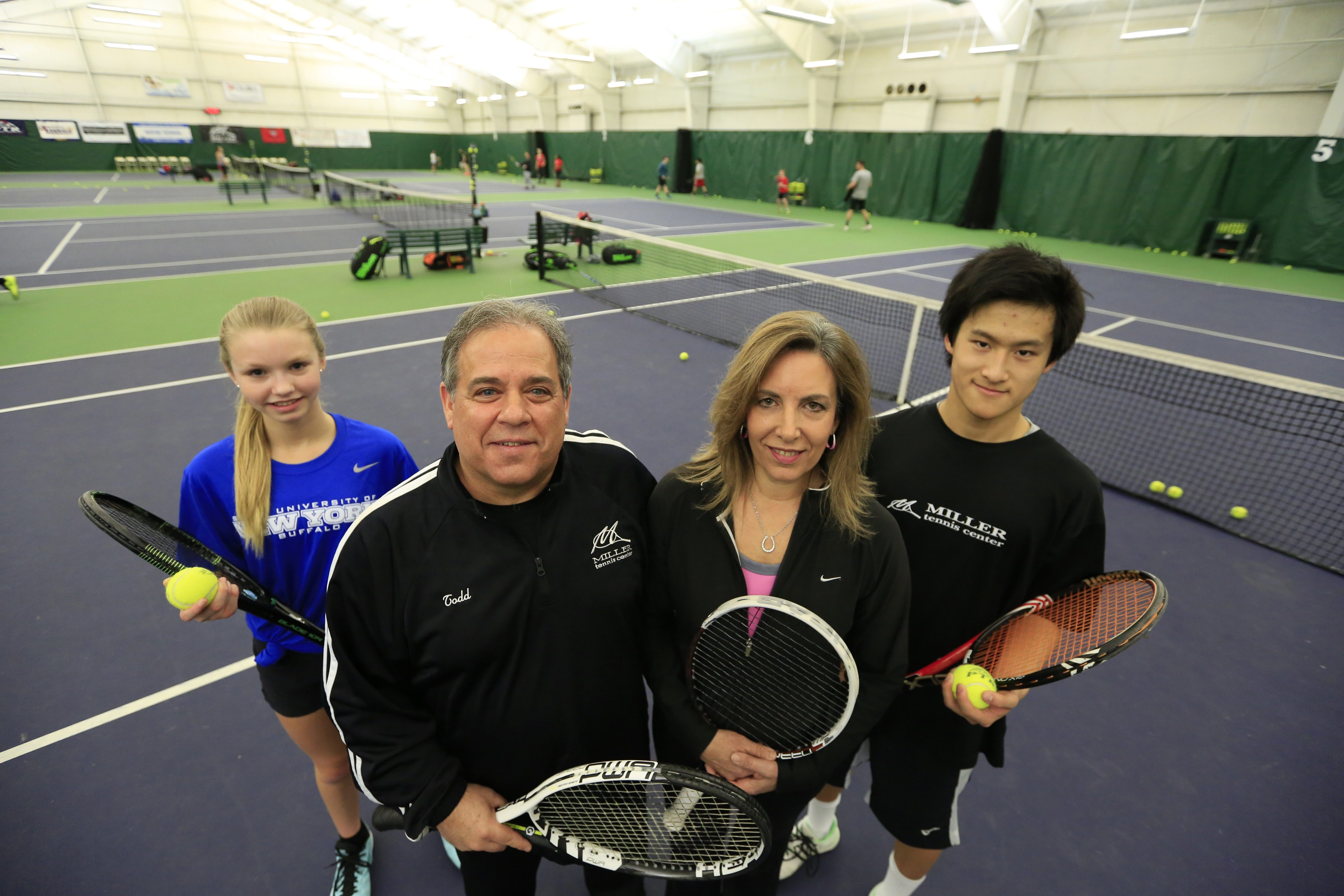 Todd and Debbie Miller, center, of the Miller Tennis Center, stand with two of their students, Jesse Hollins, left, and Harry Wang, at the Buffalo Tennis Academy.