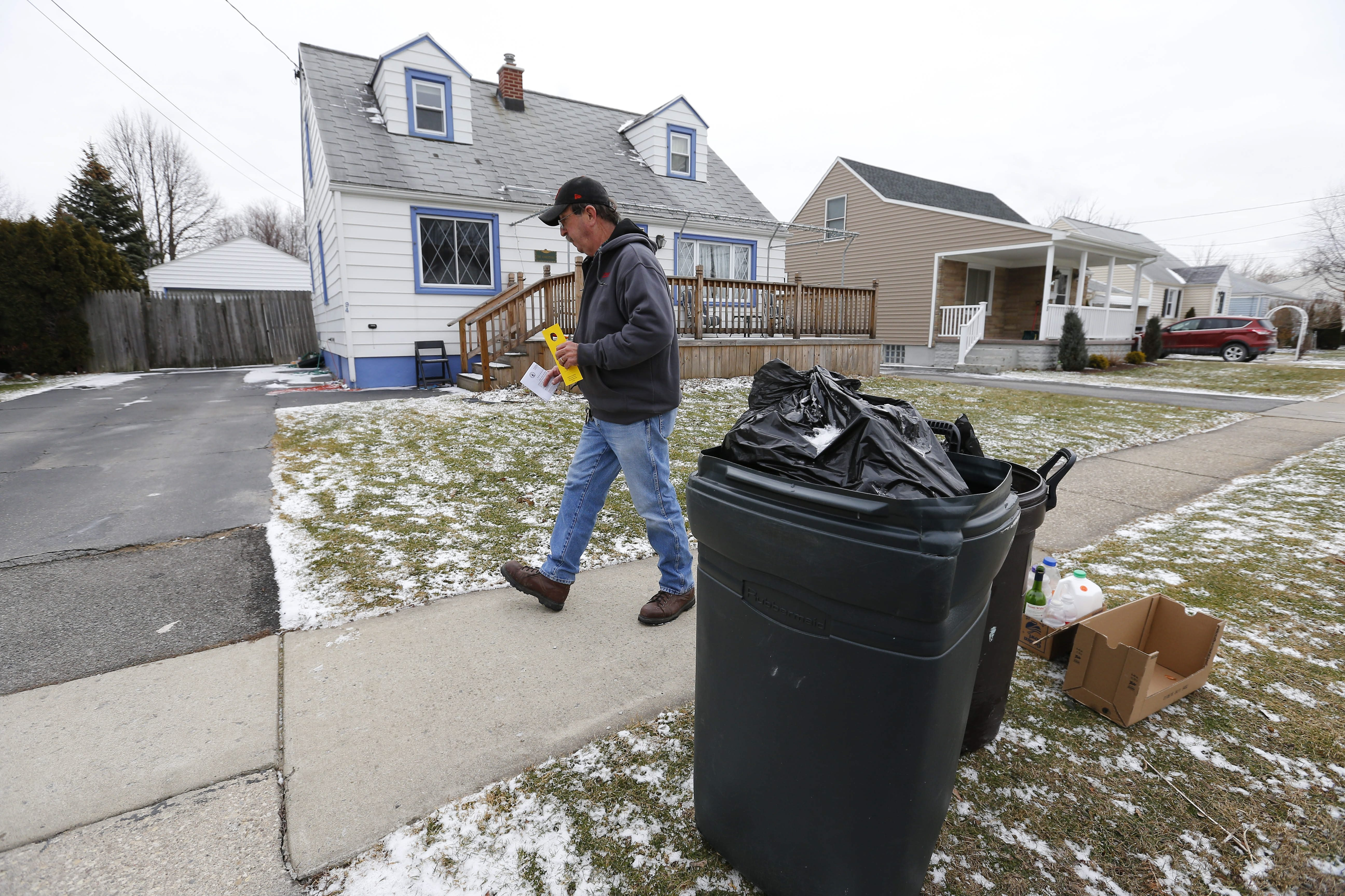 Jim Smith leaves a notice of a violation on open trash cans in the Village of Lancaster Thursday.