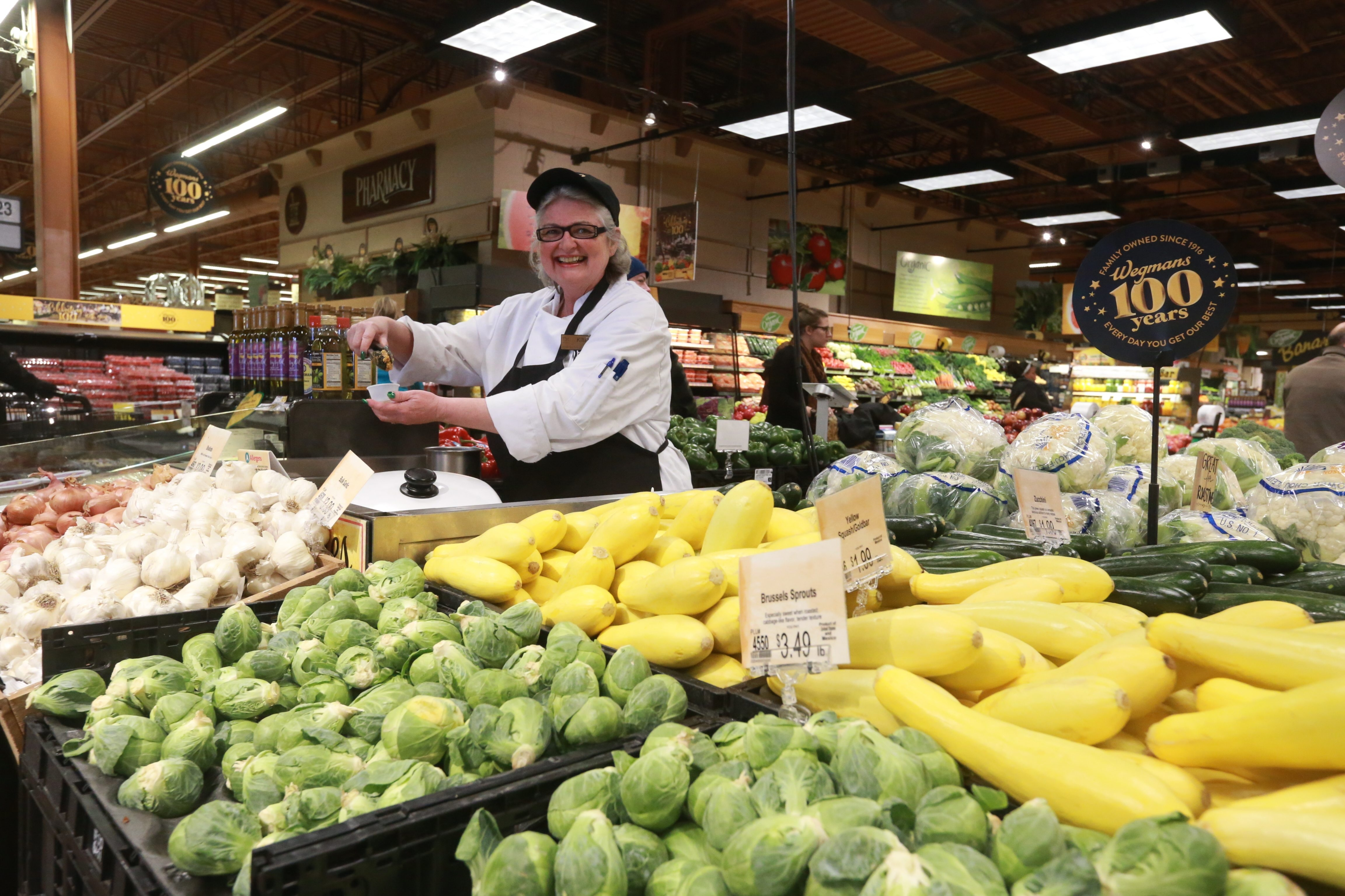 Kim Durak, a Wegmans produce worker at Amherst Street store, reflects pride in chain's No.4 rating on national list.