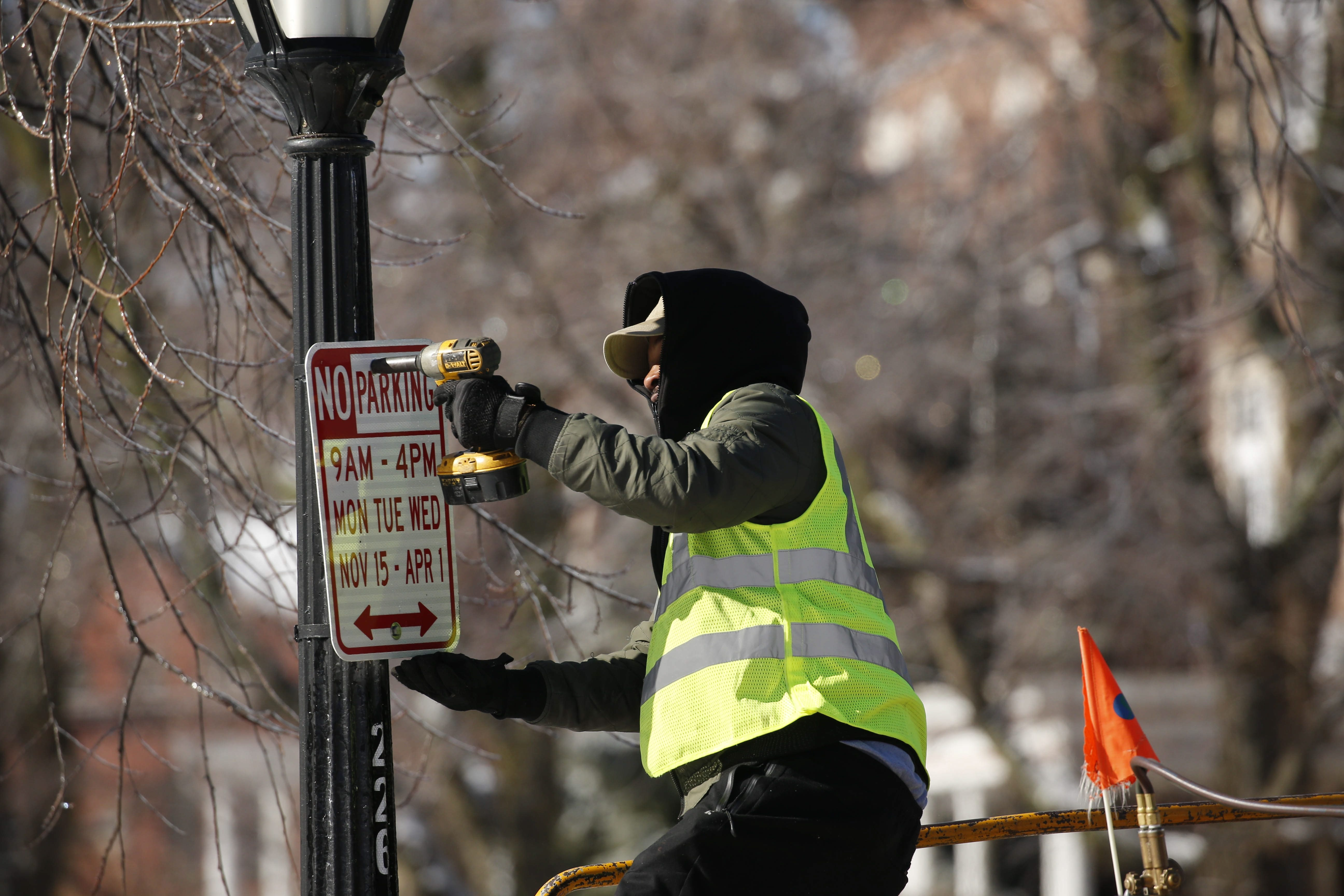 "Buffalo Public Works employee Anthony Rose replaces ""no parking"" signs with new ones reflecting new regulations on Bidwell Parkway Wednesday."