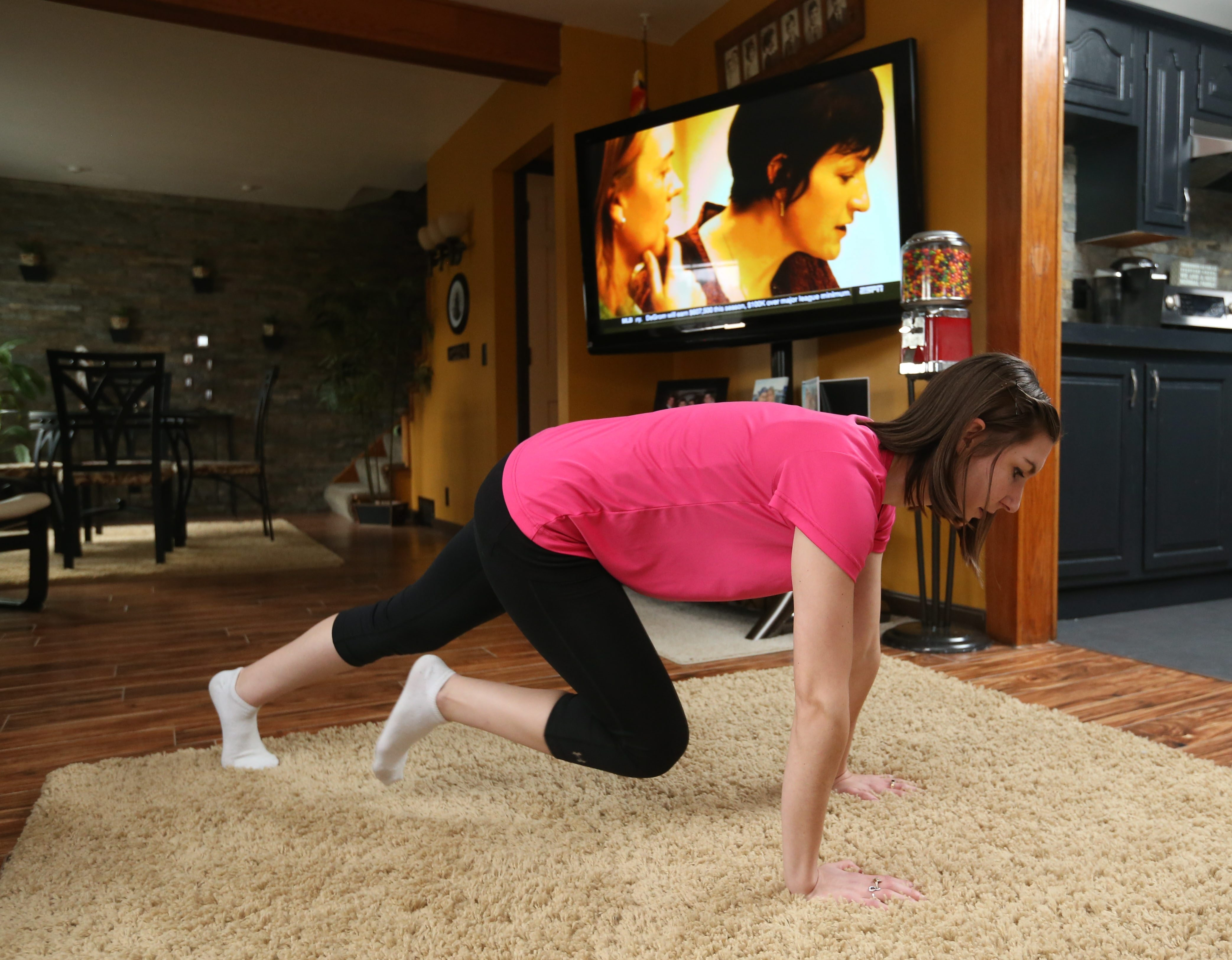 There are exercises that can be done during commercial breaks while watching TV to make it a healthier pastime.  Certified Personal Trainer Jilyana Baumgarten demonstrates mountain climbers, Friday, March 4, 2016. This is a level two exercise. (Sharon Cantillon/Buffalo News)