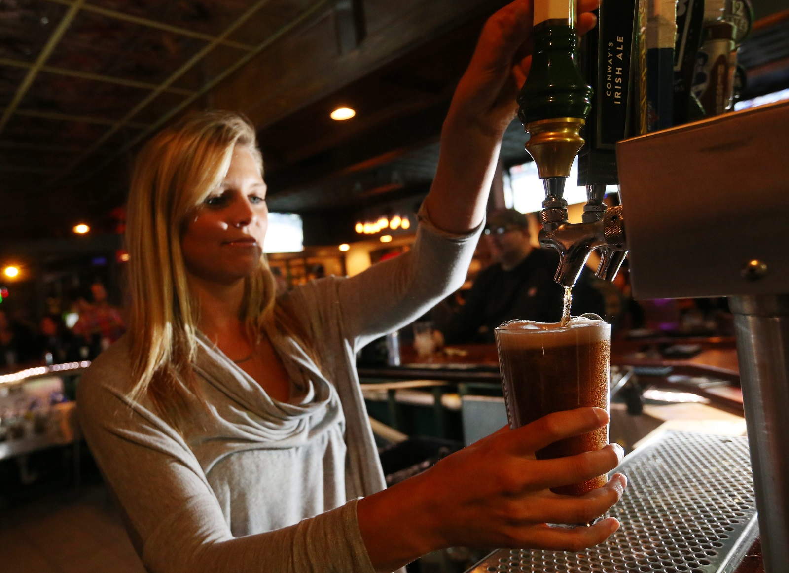 Doc Sullivan's bartender Samantha Soltis pours a glass of Smithwick's, an imported Irish Ale.  (Sharon Cantillon/Buffalo News)