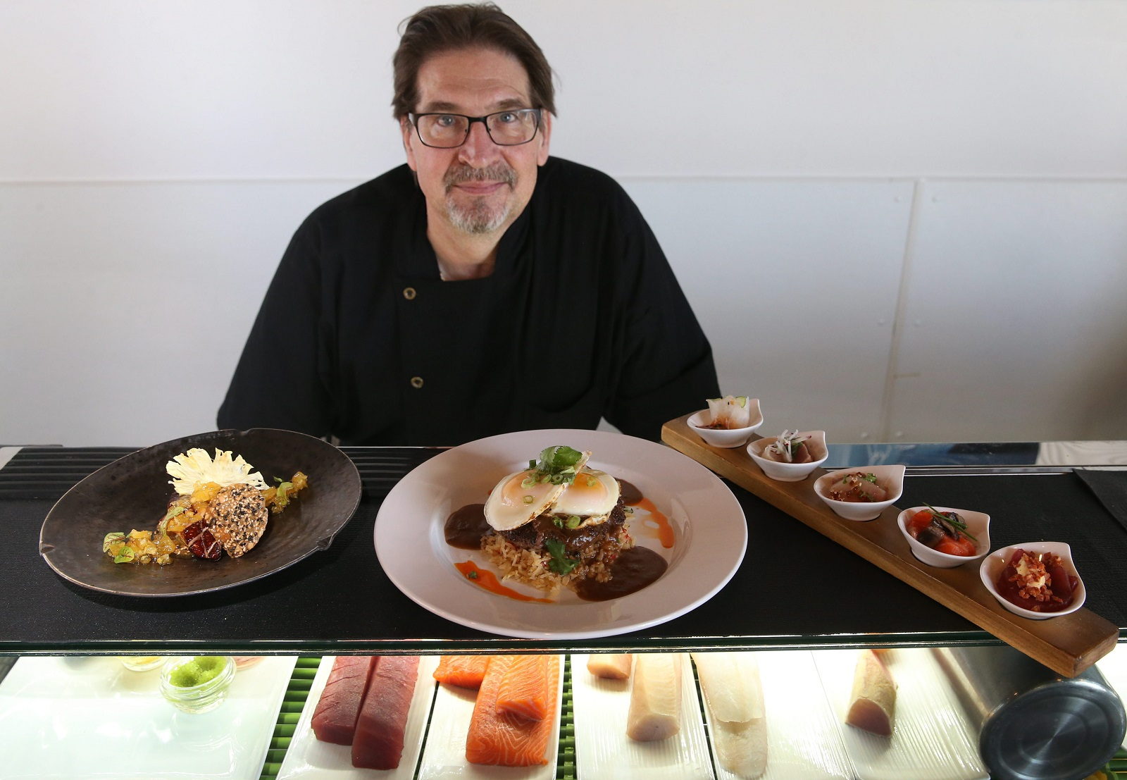 Chef Mike Andrzejewski poses in front of several dishes from SeaBar. (Sharon Cantillon/Buffalo News)