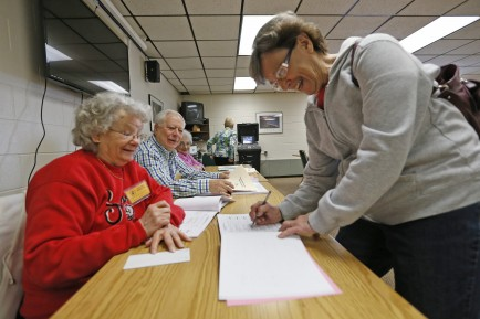 Karen Roberts signs in to vote at Cheektowaga Senior Center. Aiding her are inspectors Irene Zamrok and Joe Cefaratti. (Robert Kirkham/Buffalo News)