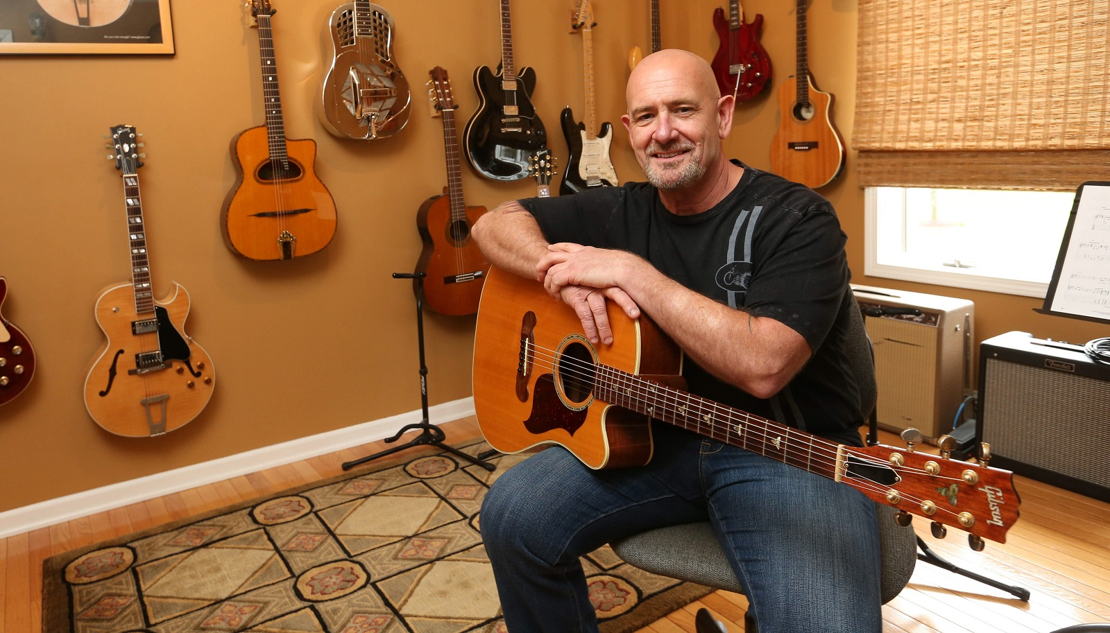 Rick Woodman has a guitar room in his house. On display are 25 or so guitars as well as harmonicas, ukuleles, a mandolin and a viola. He goes in there to play and relax. (Sharon Cantillon/Buffalo News)