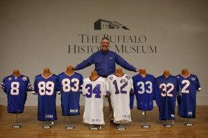 Greg Tranter with eight of his favorite Bills gameday jerseys on display at the Buffalo History Museum, Tuesday, April 26, 2016. They were worn by, from left, Brian Moorman (8) in 2009, Steve Tasker (89) in 1994, Andre Reed (83) in 1992, Thurman Thomas (34) in 1993, Jim Kelly (12) in 1994, Art Baker (33) in 1961, O.J. Simpson (32) in 1973 and Steve Christie (2) in 1994. (Derek Gee/Buffalo News)