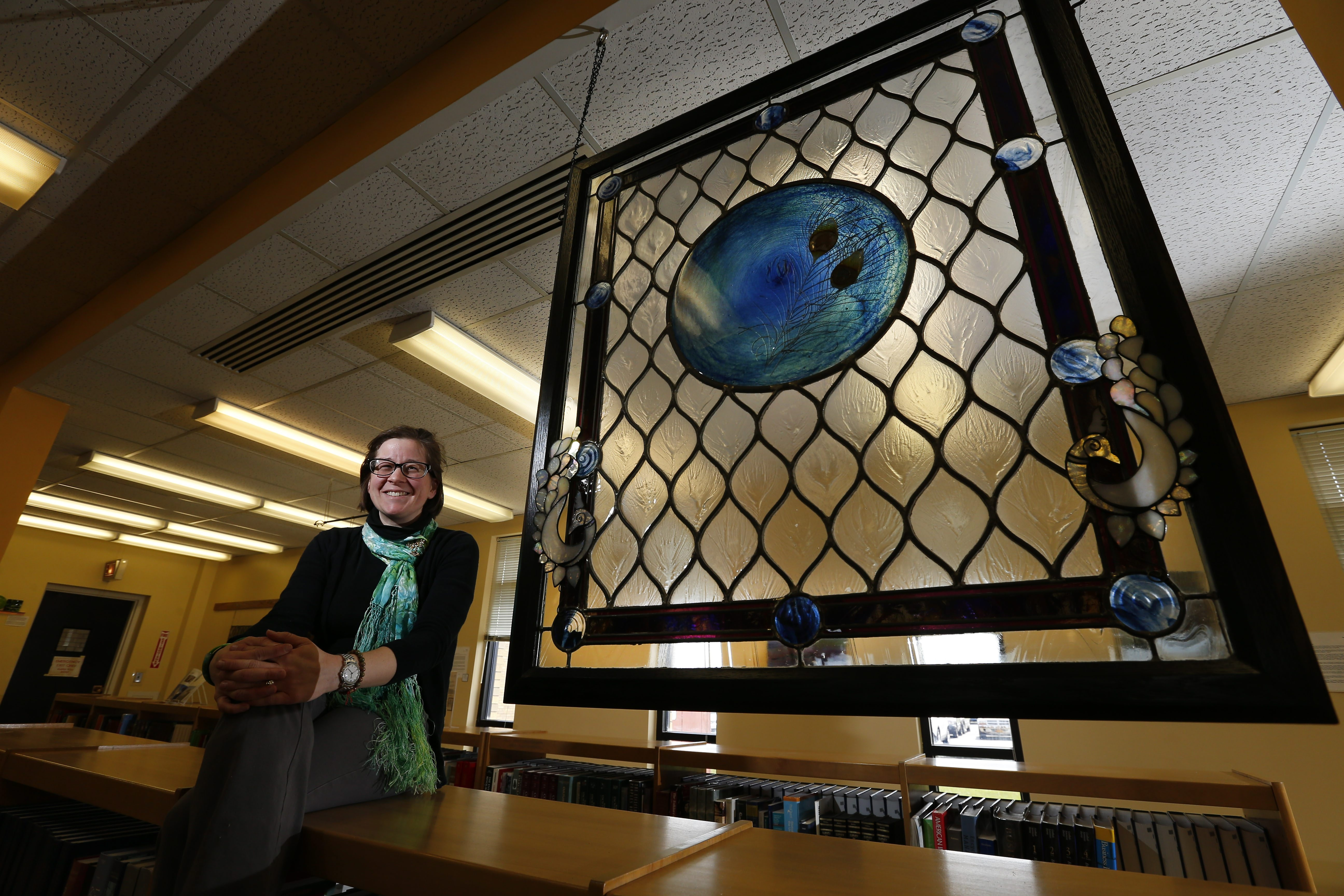 Glass craftsman Megan McElf with her piece hung for Arts in the Library at McGrath Library on the Hilbert College campus in Hamburg Tuesday.  See a photo gallery at buffalonews.com.