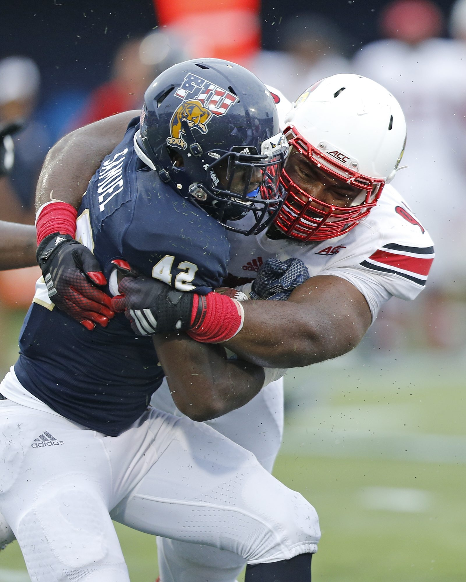 Sheldon Rankins (98) of the Louisville Cardinals tackles Anthon Samuel (42) of the Florida Panthers on Sept. 20, 2014.