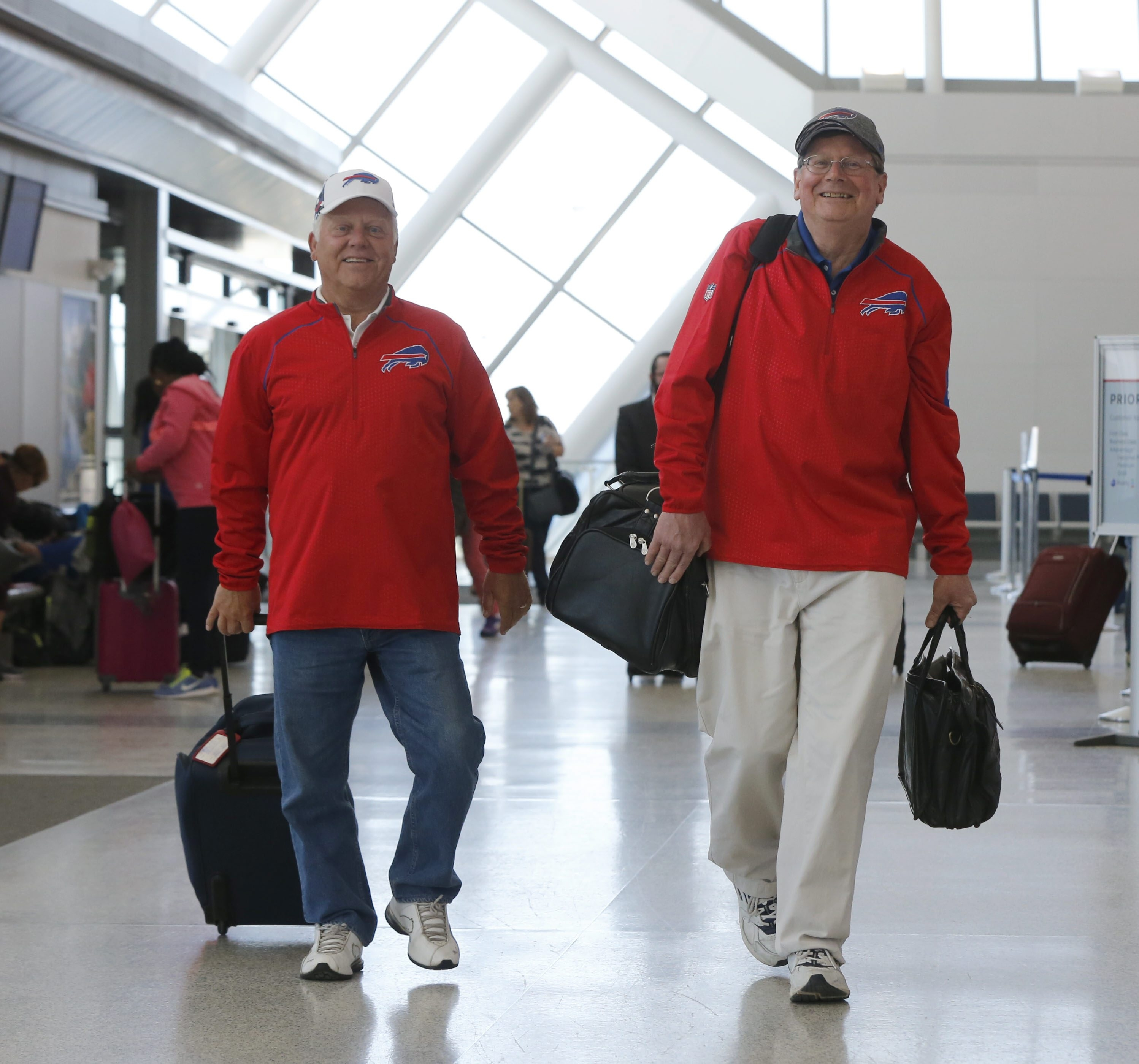 Mike Naab, left,  joins his friend Mark Derringer for a flight to Chicago after Derringer became the winner of a lottery among Bills season ticket-holders and will be the team's fan representative at the NFL Draft. (Harry Scull Jr./Buffalo News)