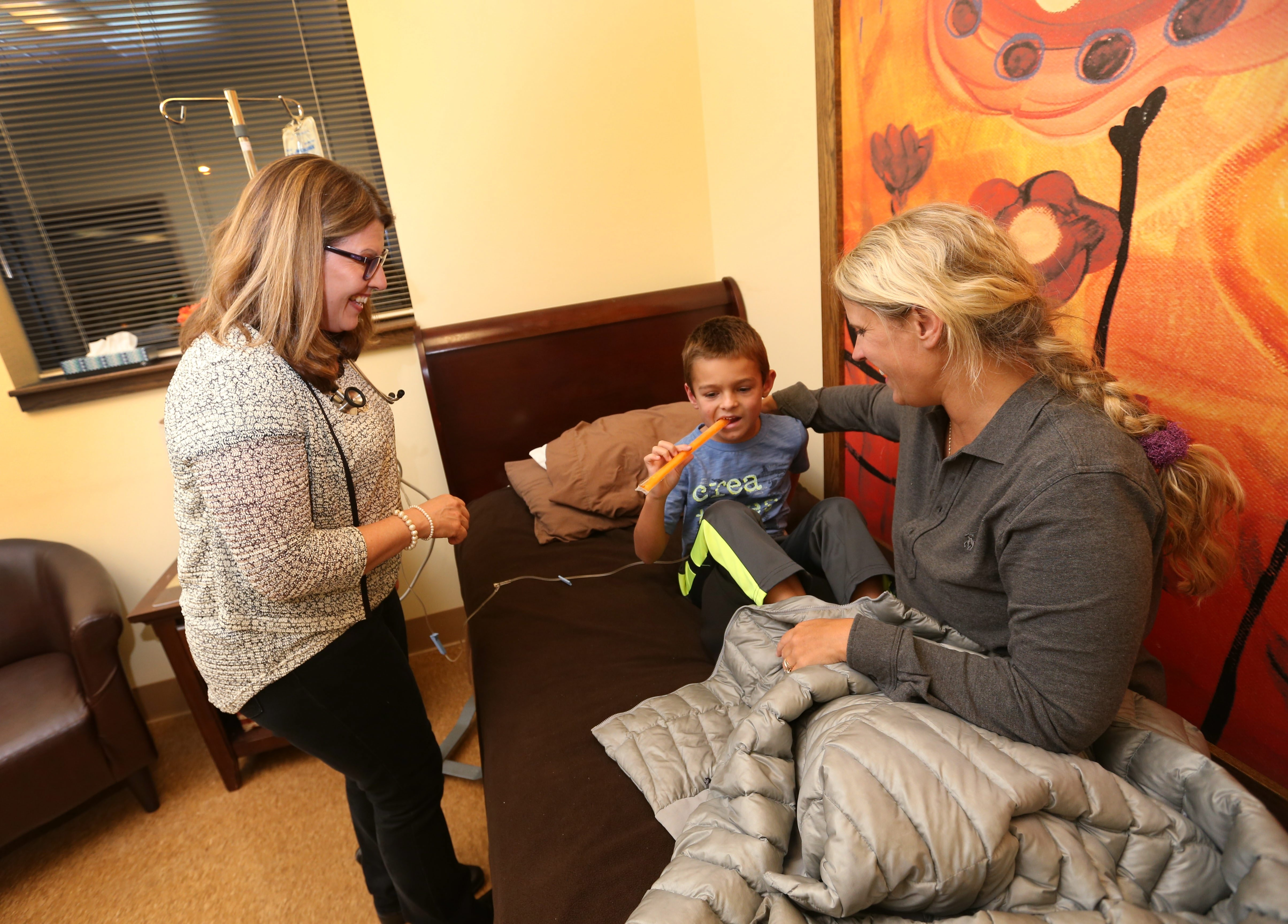 Nurse practitioner Becky Roloff brings a popsicle to  Andrew Jakubowski, 6, of Lancaster, while caring for him at Pediatric  & Adolescent Urgent Care of WNY, which is open on nights and weekends to give families an alternative to the emergency room.  His mom Kristen Jakubowski sits on the bed with him as he gets an IV. (Sharon Cantillon/Buffalo News)