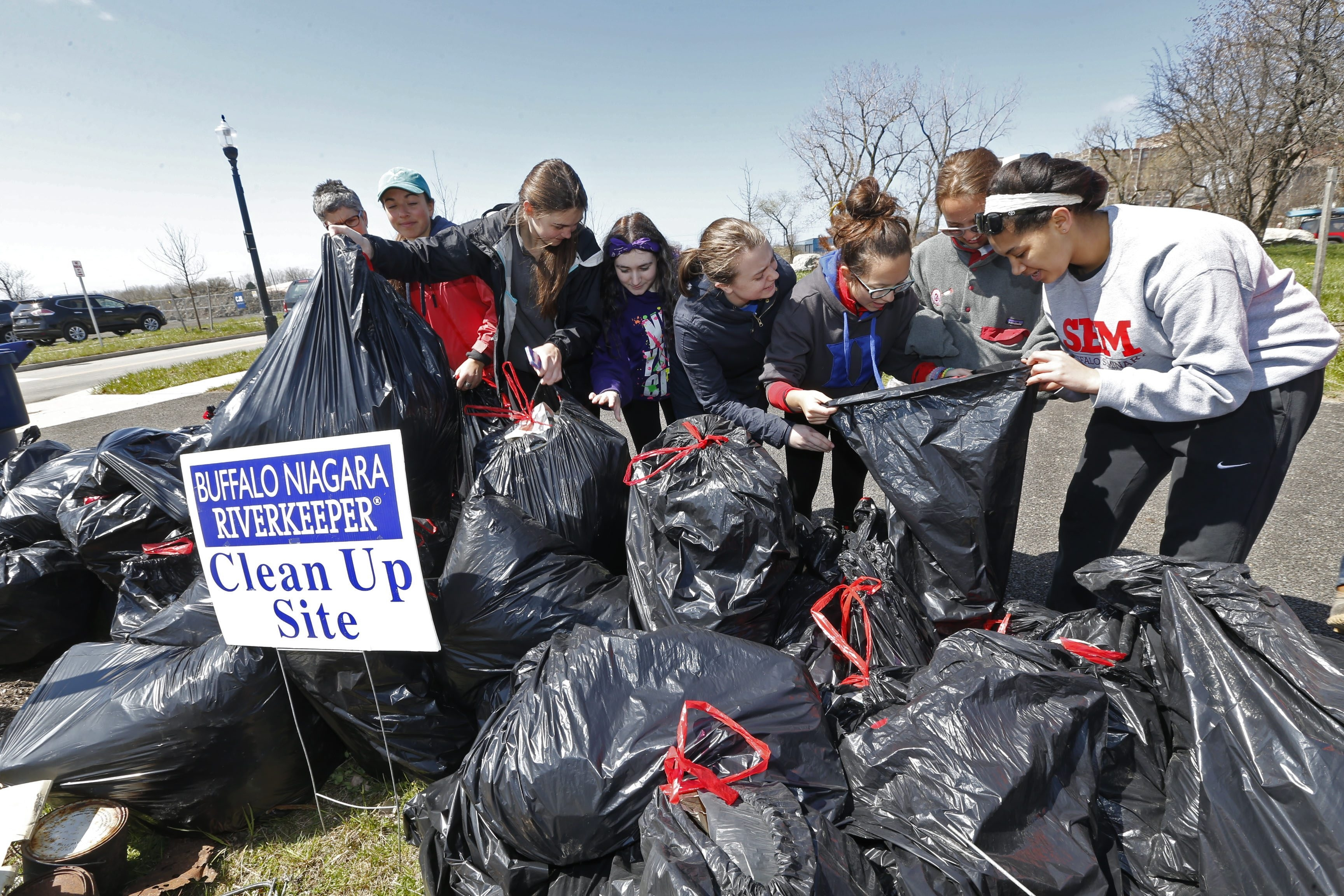 Students, staff and parents from Buffalo Seminary tie up bags after they collected trash along the shoreline near Ohio Street as part of Buffalo Niagara Riverkeeper's annual spring cleanup. A record 1,500 volunteers participated.