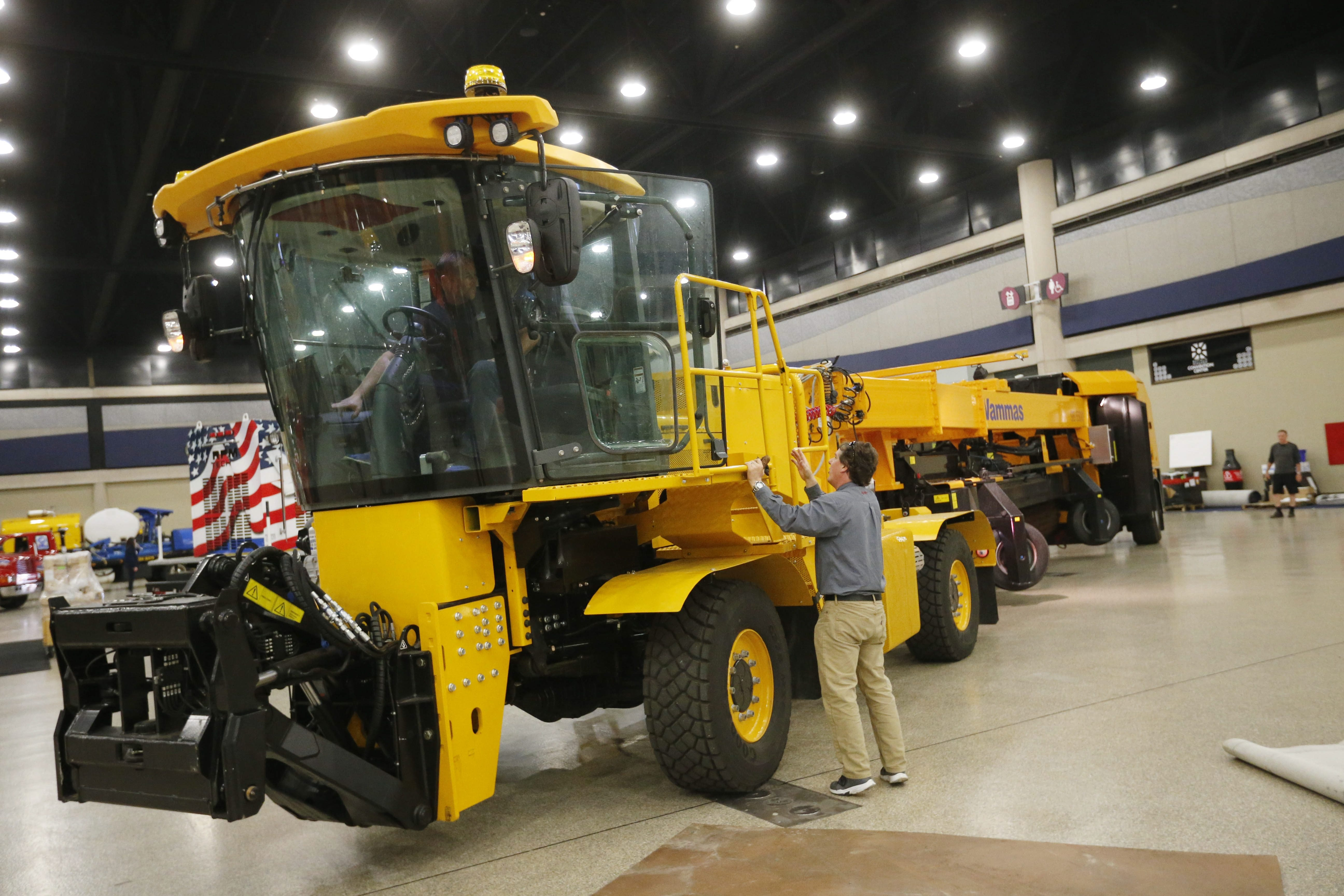 Roger Huot, right, of Fortbrand Services, gives driver Matt Roorda of Roorda Transport instructions as he drives a giant sweeper into place during the setup for the International Aviation Snow Symposium at the Buffalo Niagara Convention Center on Friday.