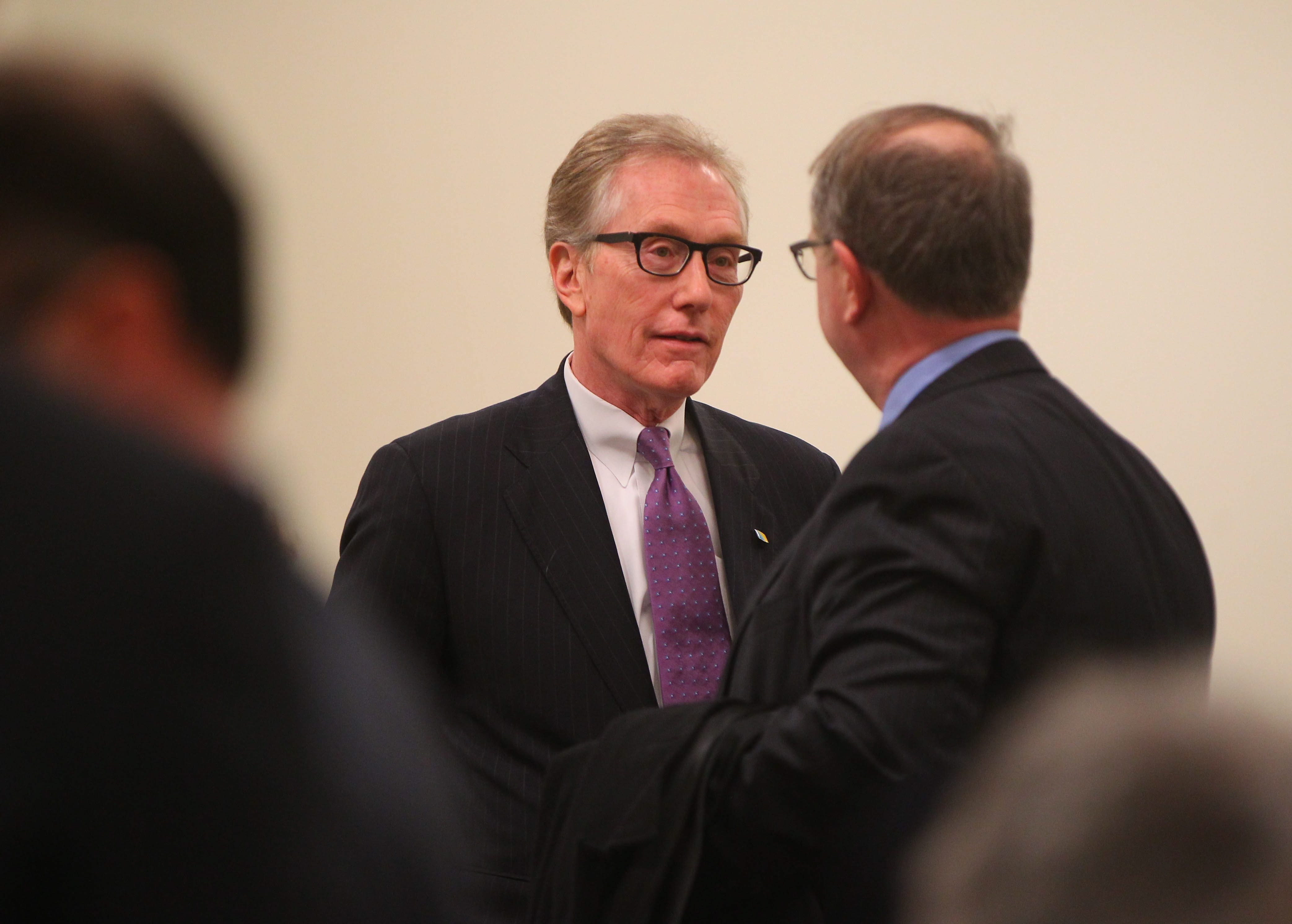 First Niagara CEO Gary Crosby, left, speaks with shareholders after a special meeting in the Larkin Exchange Building in Buffalo last month.