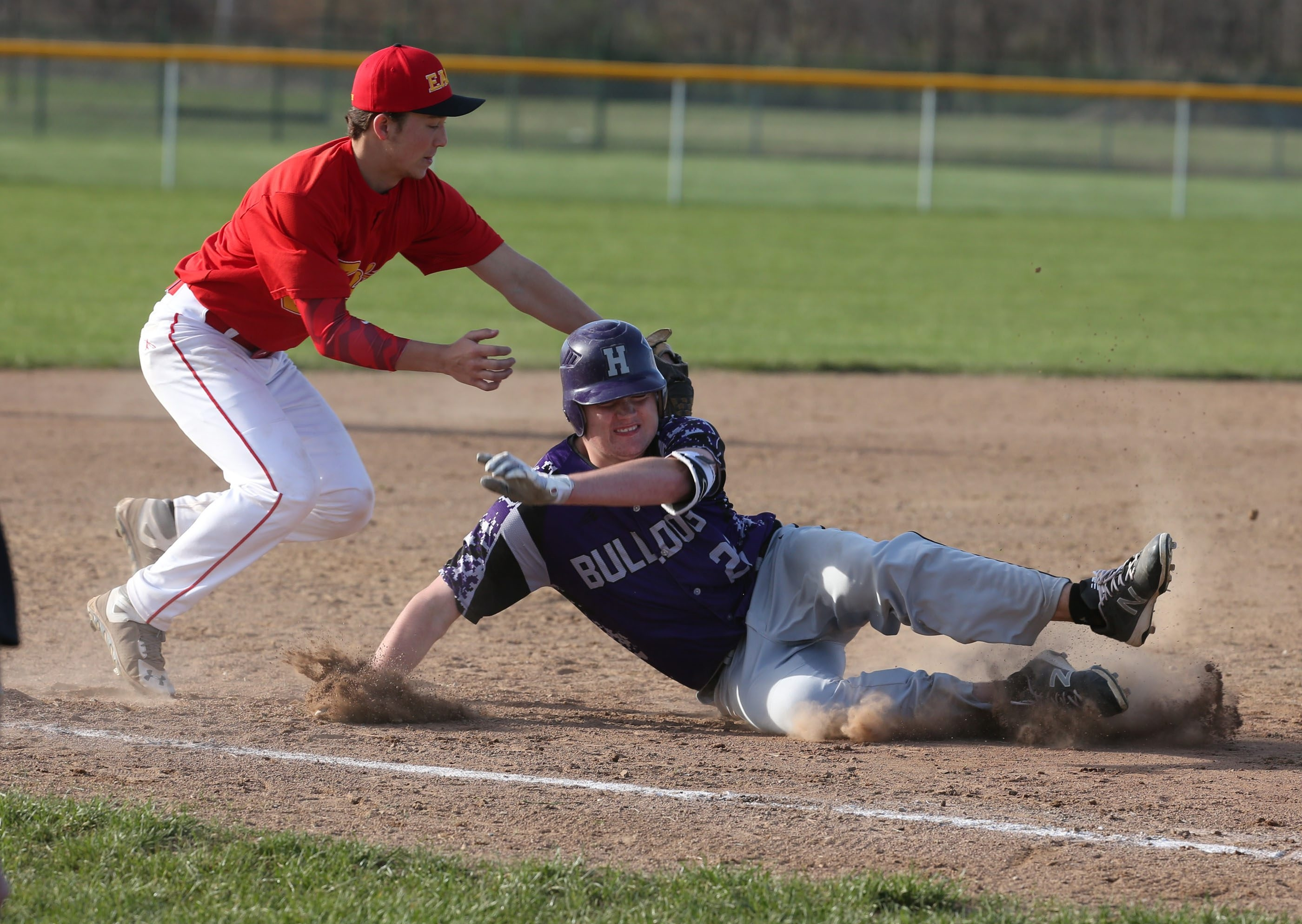 Hamburg's Shawn Filas slides safely into third base on a steal against Williamsville East's Ryan Foster on Tuesday in Hamburg.