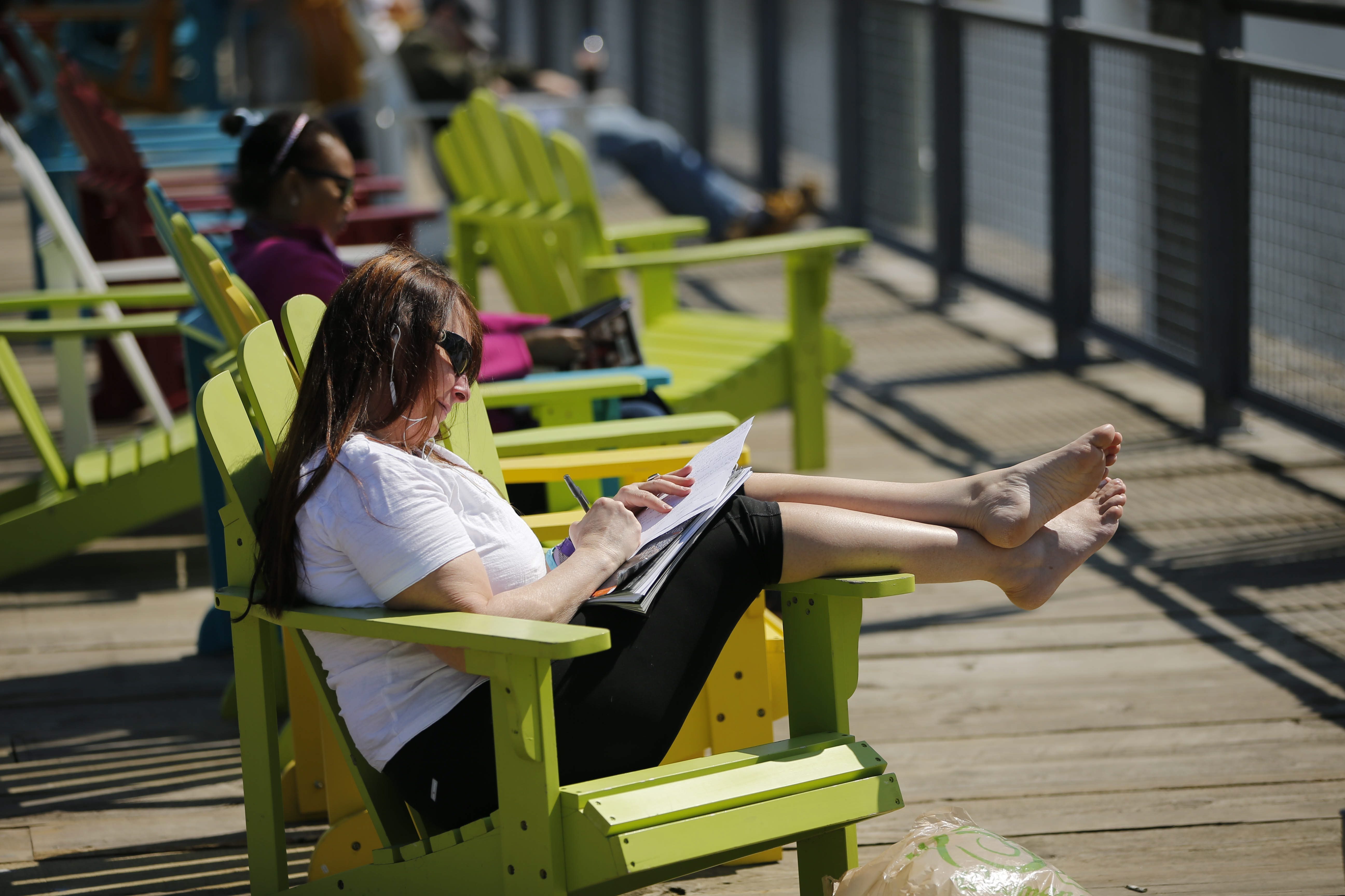 Lori Carvelli of Buffalo seizes the opportunity to soak up the sunshine Friday at Canalside, stretching out in a chair on the boardwalk while doing some writing and enjoying the weather.