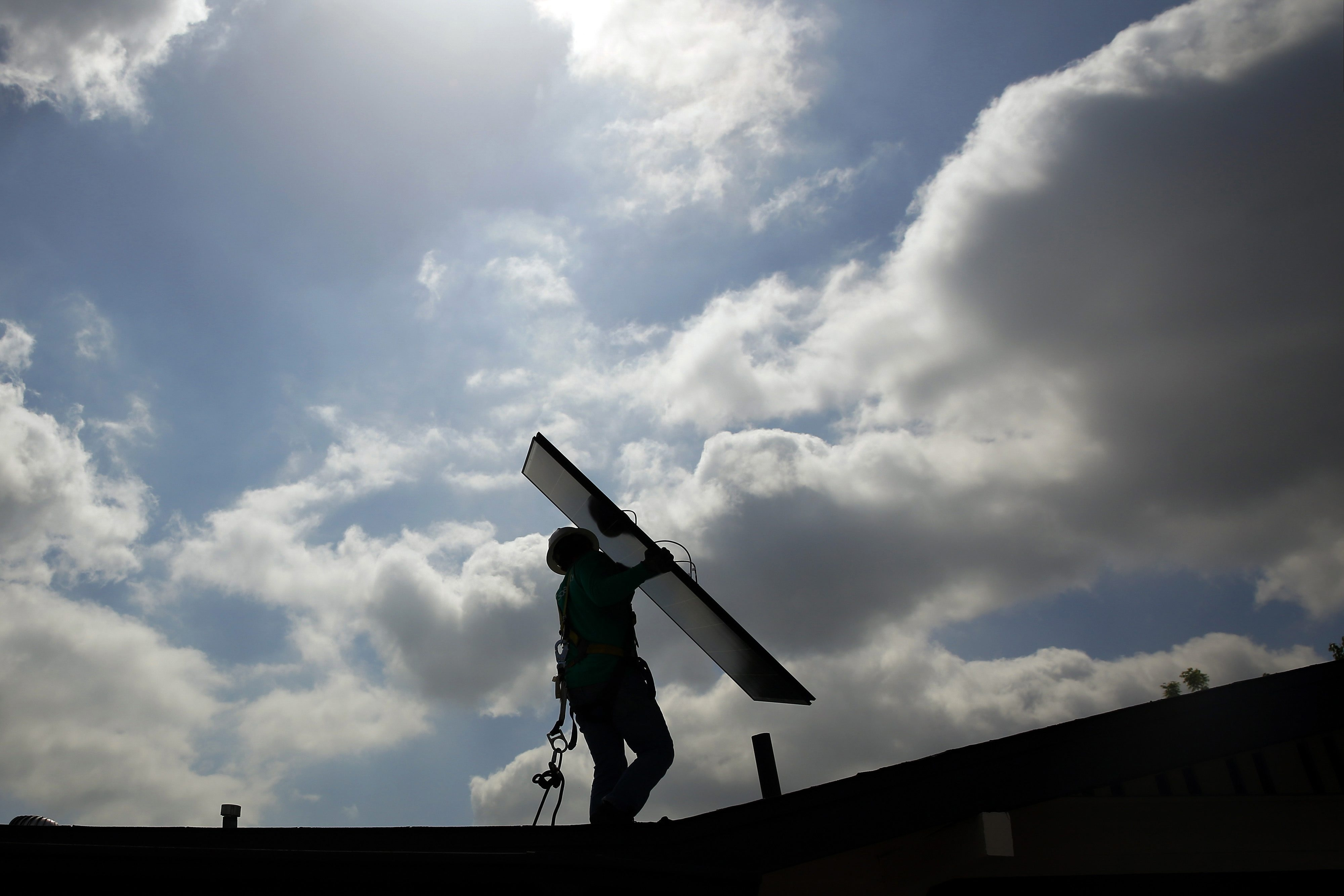A SolarCity Corp. employee carries a solar panel during an installation at a home in Los Angeles. The company is planning to start installing in Pittsburgh, the closest to Buffalo yet for the company. (Bloomberg photo)