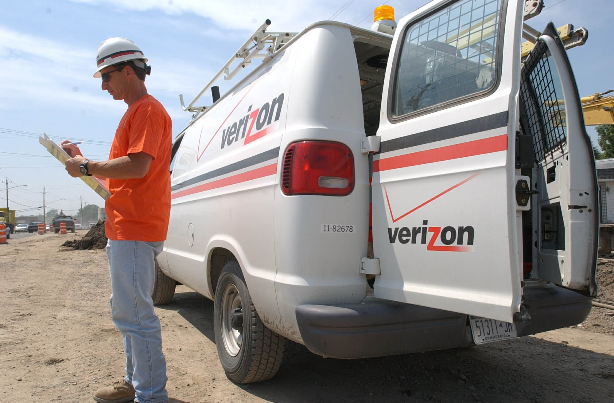 Verizon inspector Nick DeFilippo takes notes on his clipboard as he oversees work on underground cables on Broadway near Dick Road.  (Robert Kirkham/News file photo)