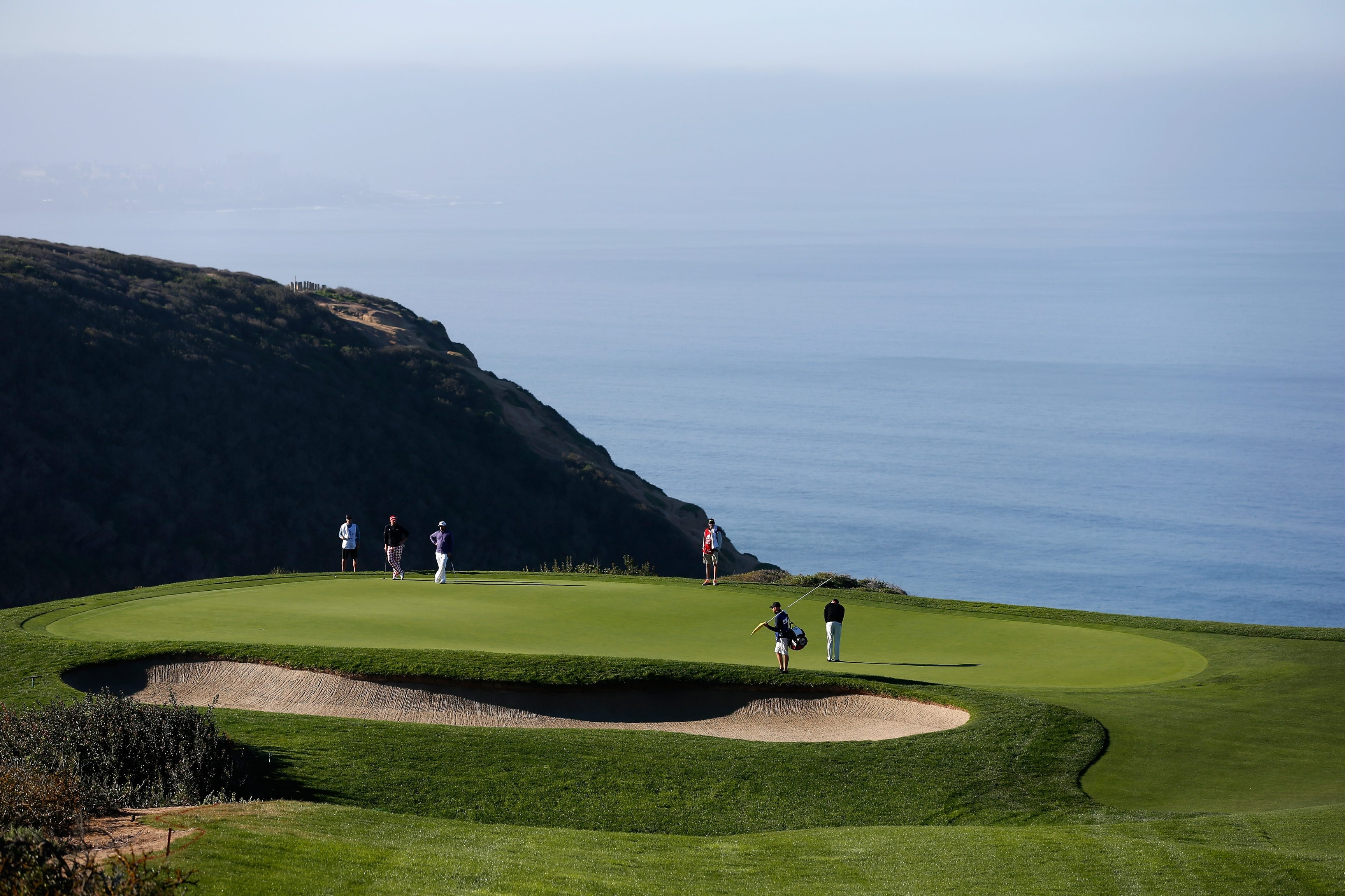 PGA Tour pros putt on the scenic third hole at Torrey Pines' South Course, a worthwhile addition to any golfer's bucket list.