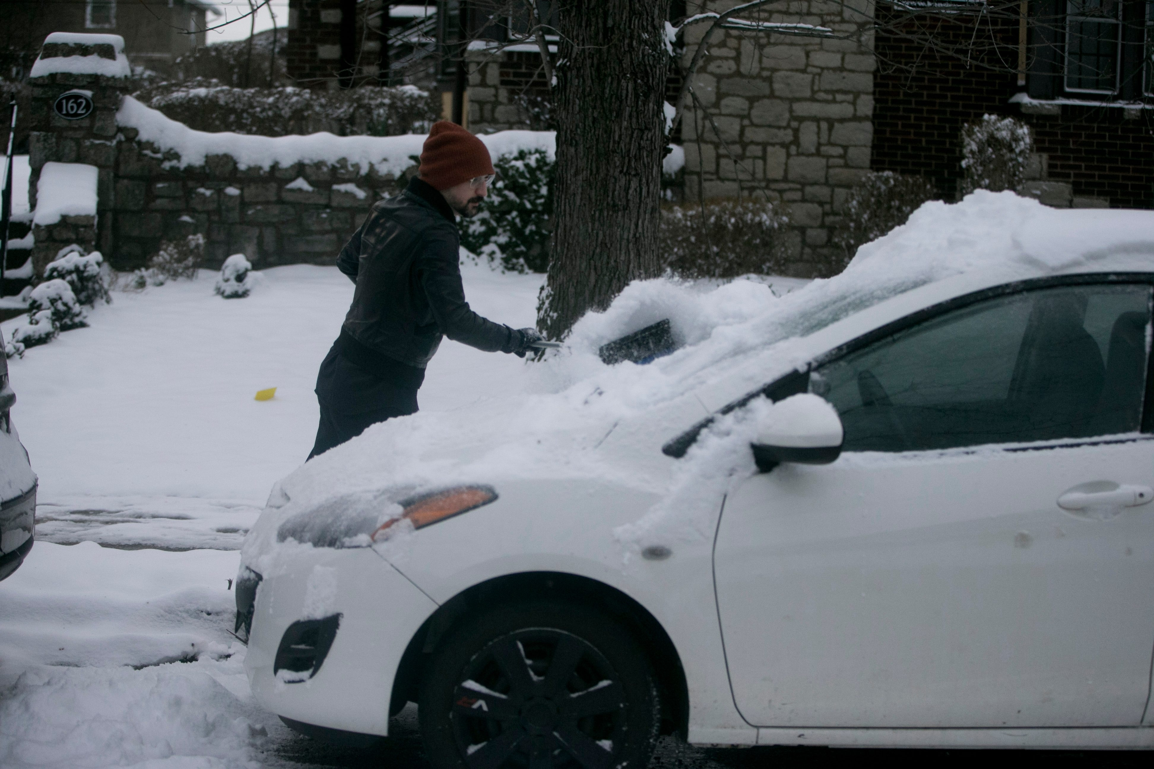 Ron Ciminelli clears off car on Sanders Road in North Buffalo after unseasonable snowfall.