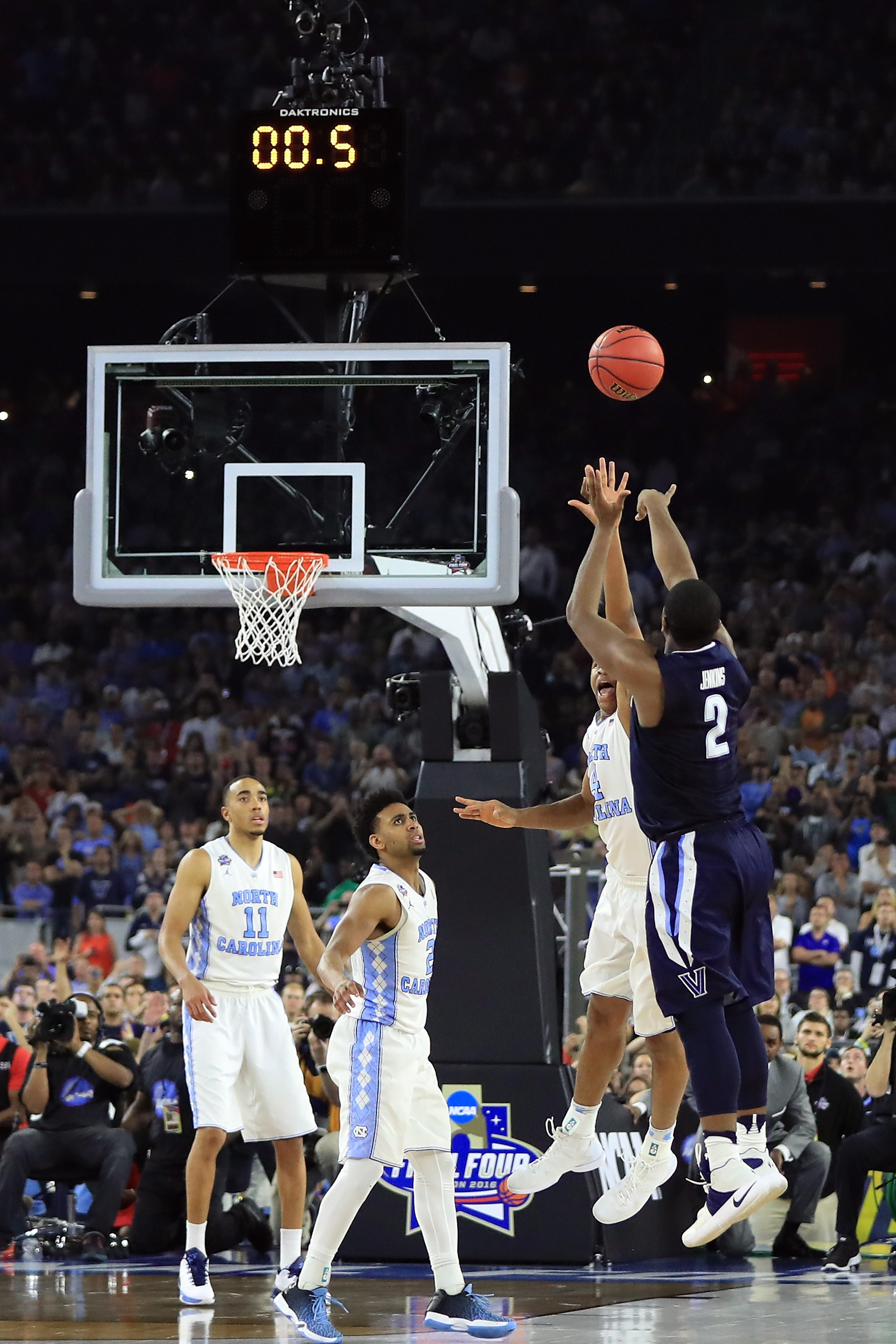 With the clock winding down, Villanova's Kris Jenkins puts up the game-winning three-pointer over North Carolina's defense.