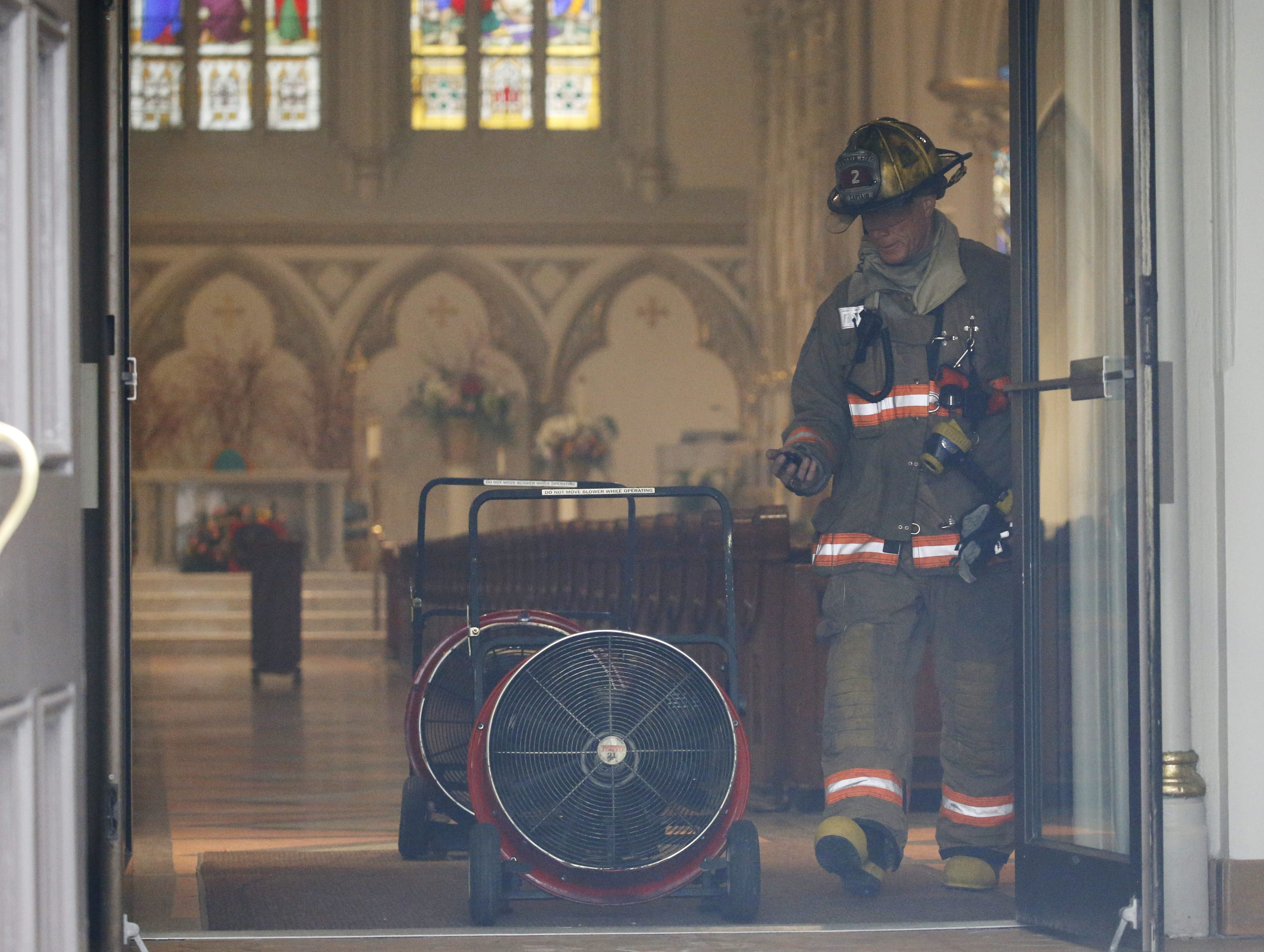 A Buffalo firefighter measures air quality as heavy duty fans clear smoke from St. Joseph Cathedral after an early morning fire, Friday, April 1, 2016.  (Derek Gee/Buffalo News)