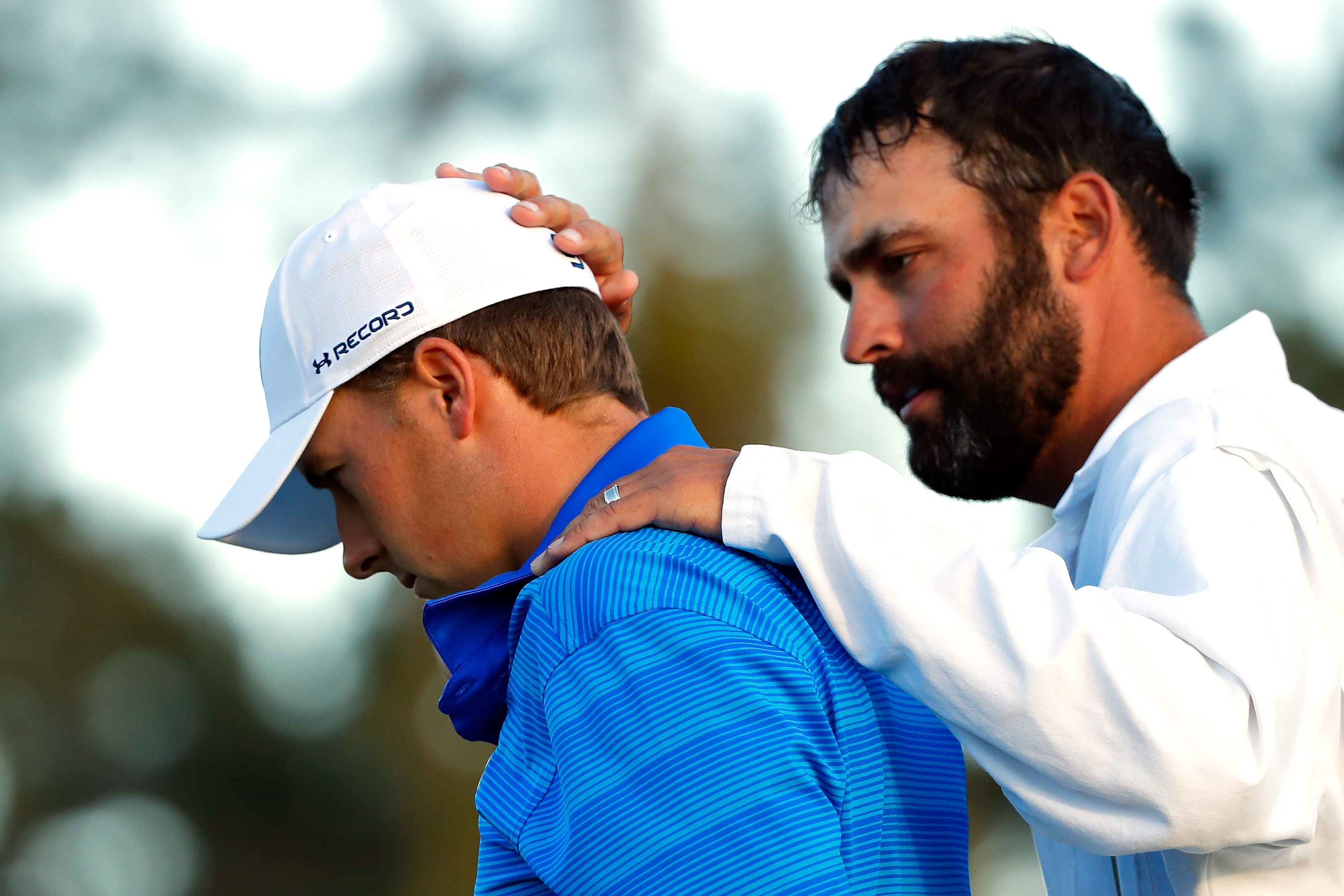 Michael Greller, Jordan Spieth's caddie, tries to comfort the young star after Spieth's meltdown on the back nine at the Masters on Sunday. (Getty Images)