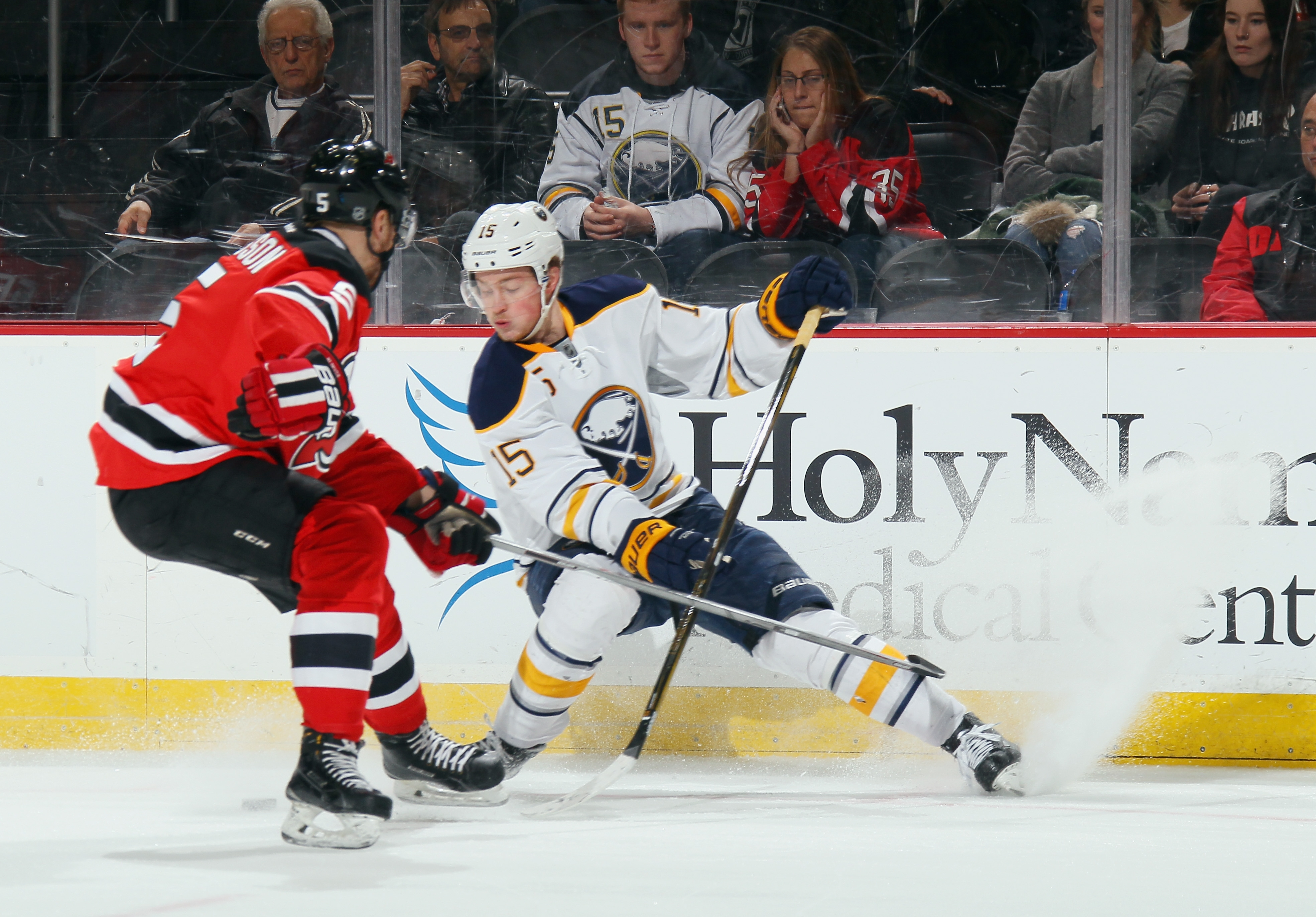 Jack Eichel fights for the puck with Adam Larsson of the Devils during the first period at the Prudential Center. Eichel had an empty-net goal in the game.
