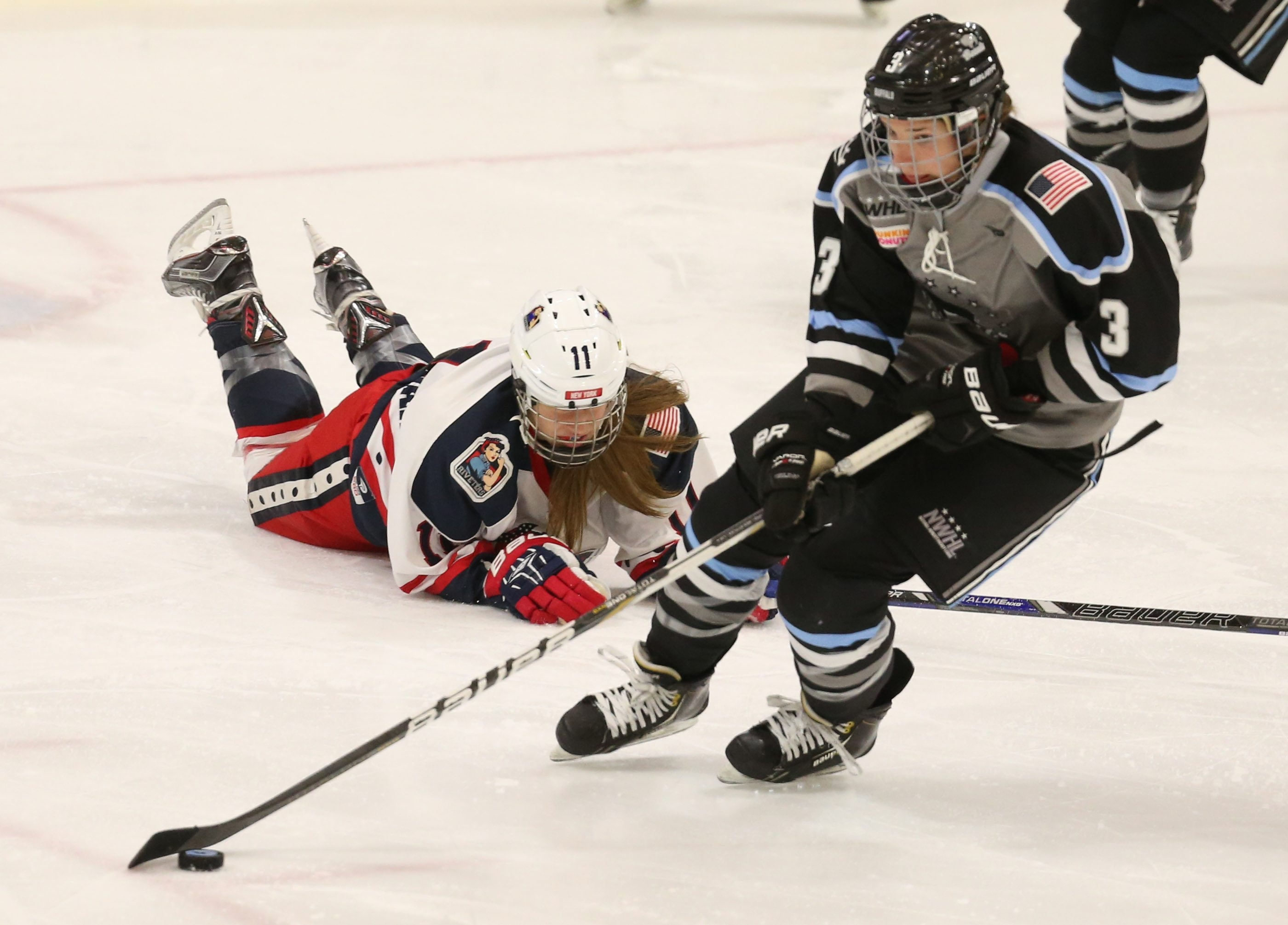 Kelly Steadman of the Buffalo Beauts, left, battles New York Riveters Morgan Fritz-Ward for the puck in a National Women's Hockey League game in February.