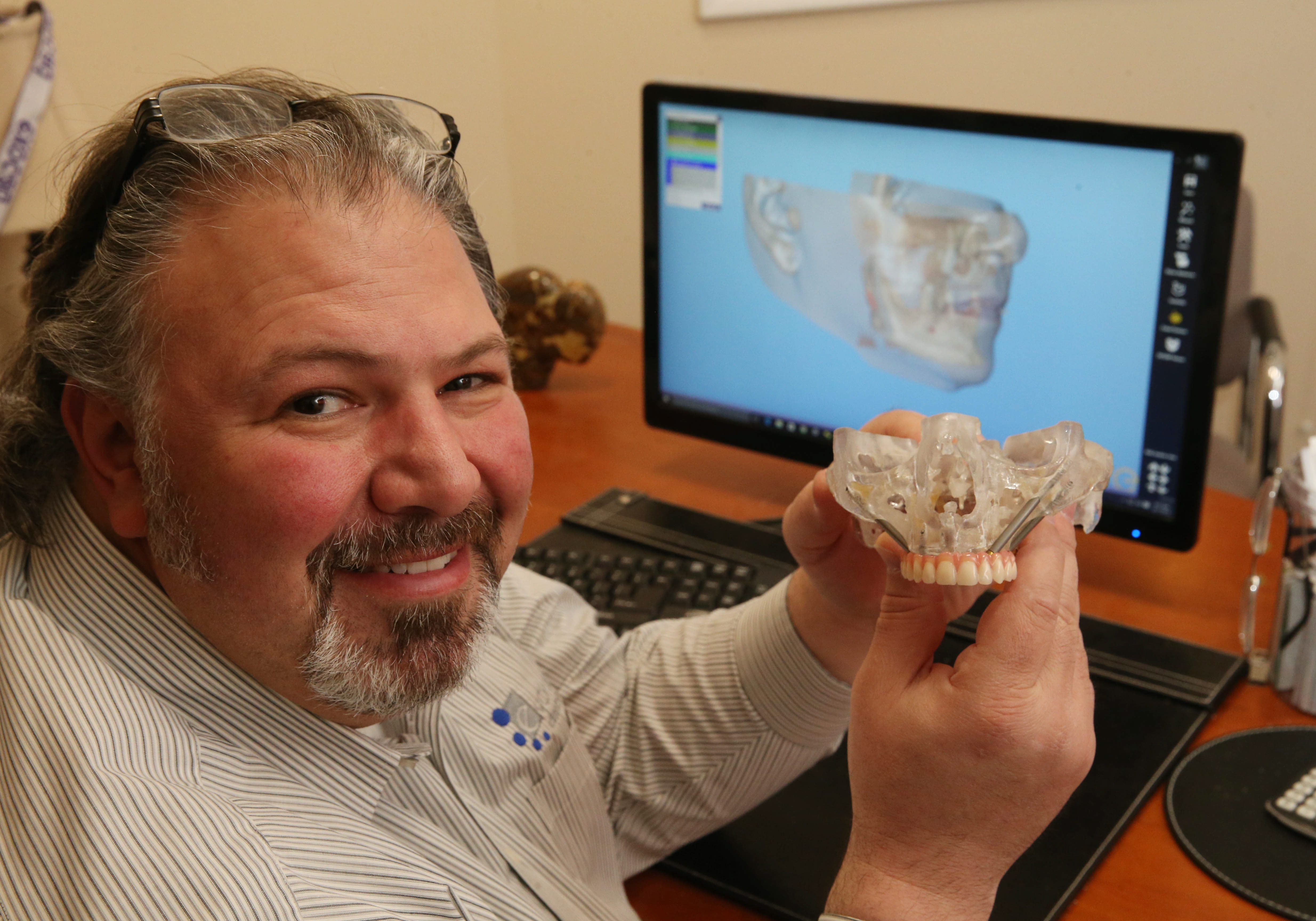 Making dentures and dental implants has become a high-tech industry.  Evolution Dental Science has transferred much of their work from the table to the computer, 3D and high tech milling machines. Chief Technology Officer John Orfanidis shows how even extreme cases of bone losses can often be worked out through the use of computer imaging. (Sharon Cantillon/Buffalo News)