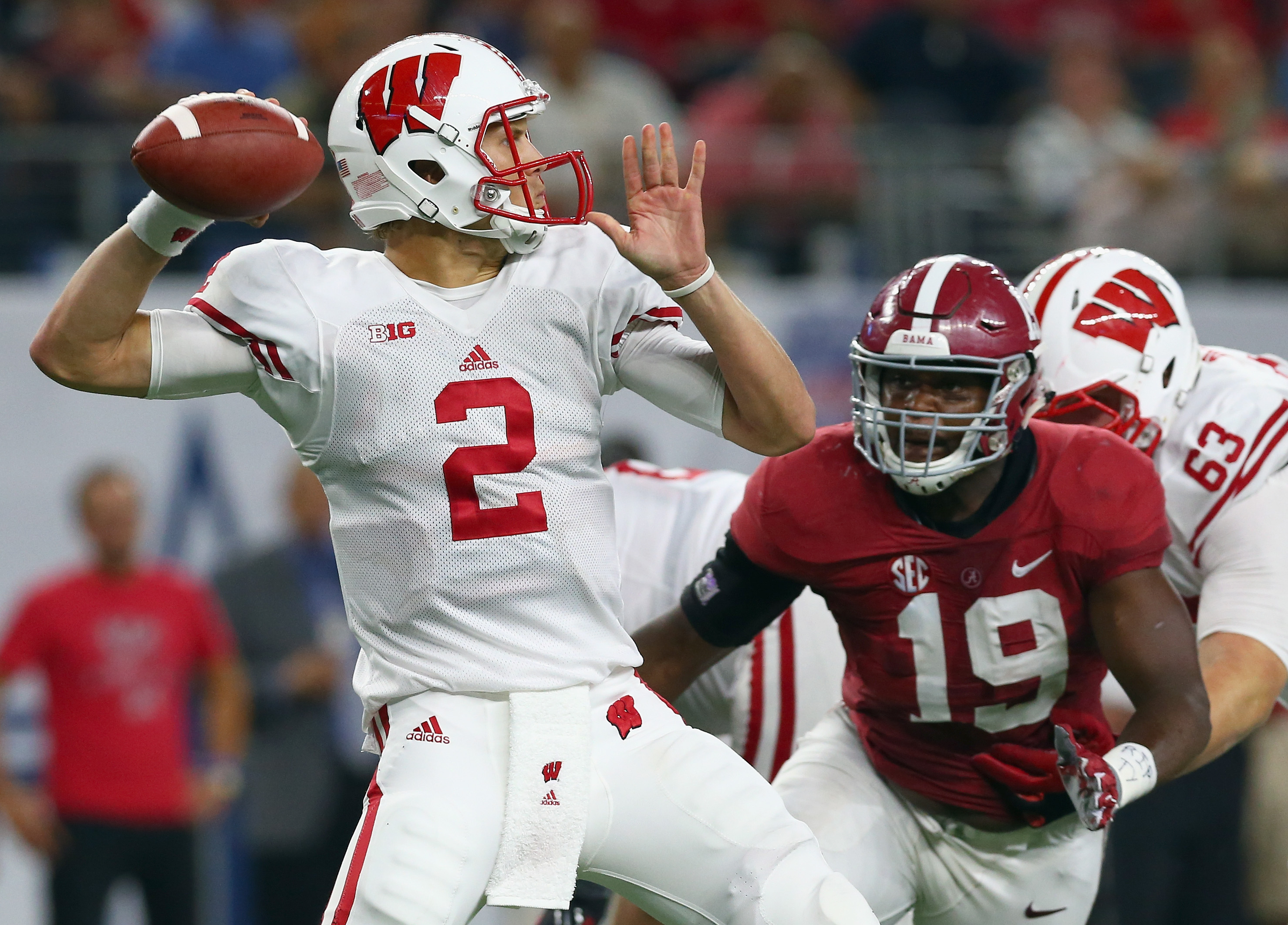 Joel Stave of Wisconsin looks for an open receiver under pressure from Reggie Ragland of Alabama on Sept. 5, 2015.  (Getty Images)