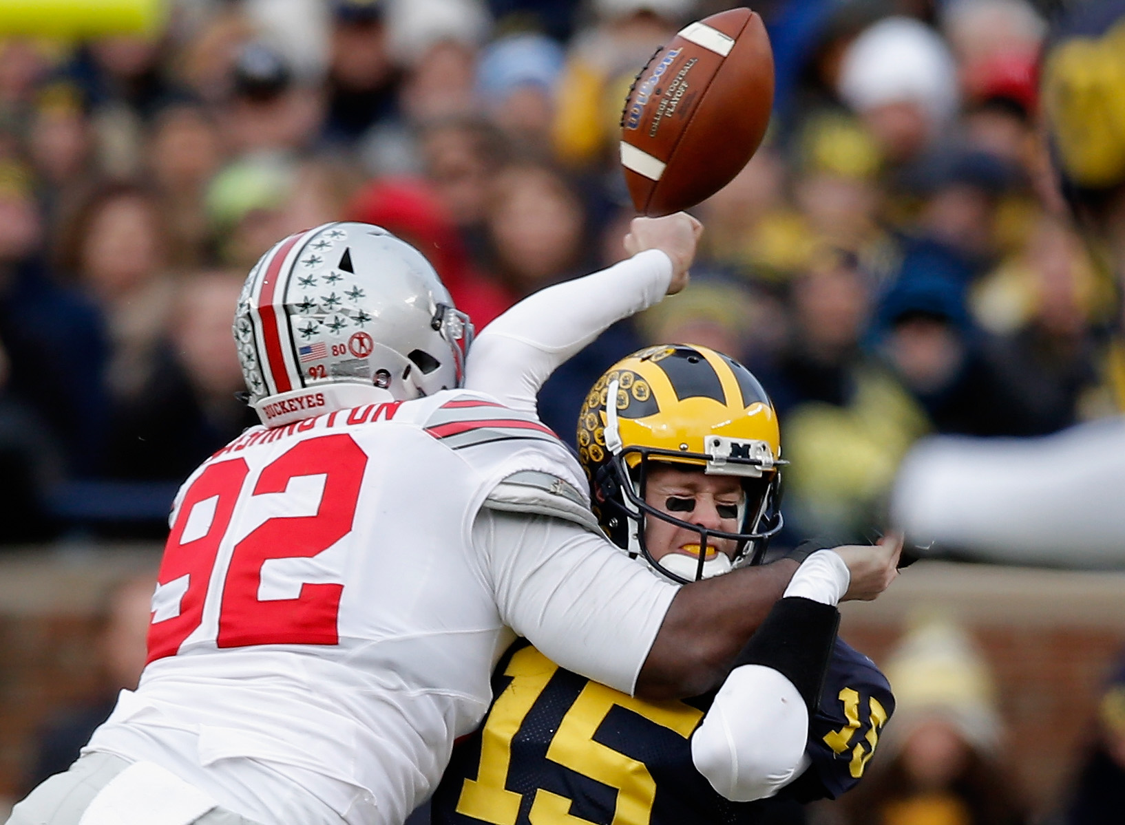 ANN ARBOR, MI - NOVEMBER 28: Quarterback Jake Rudock #15 of the Michigan Wolverines fumbles the ball while being hit by Adolphus Washington #92 of the Ohio State Buckeyes in the third quarter at Michigan Stadium on November 28, 2015 in Ann Arbor, Michigan.  (Photo by Gregory Shamus/Getty Images)